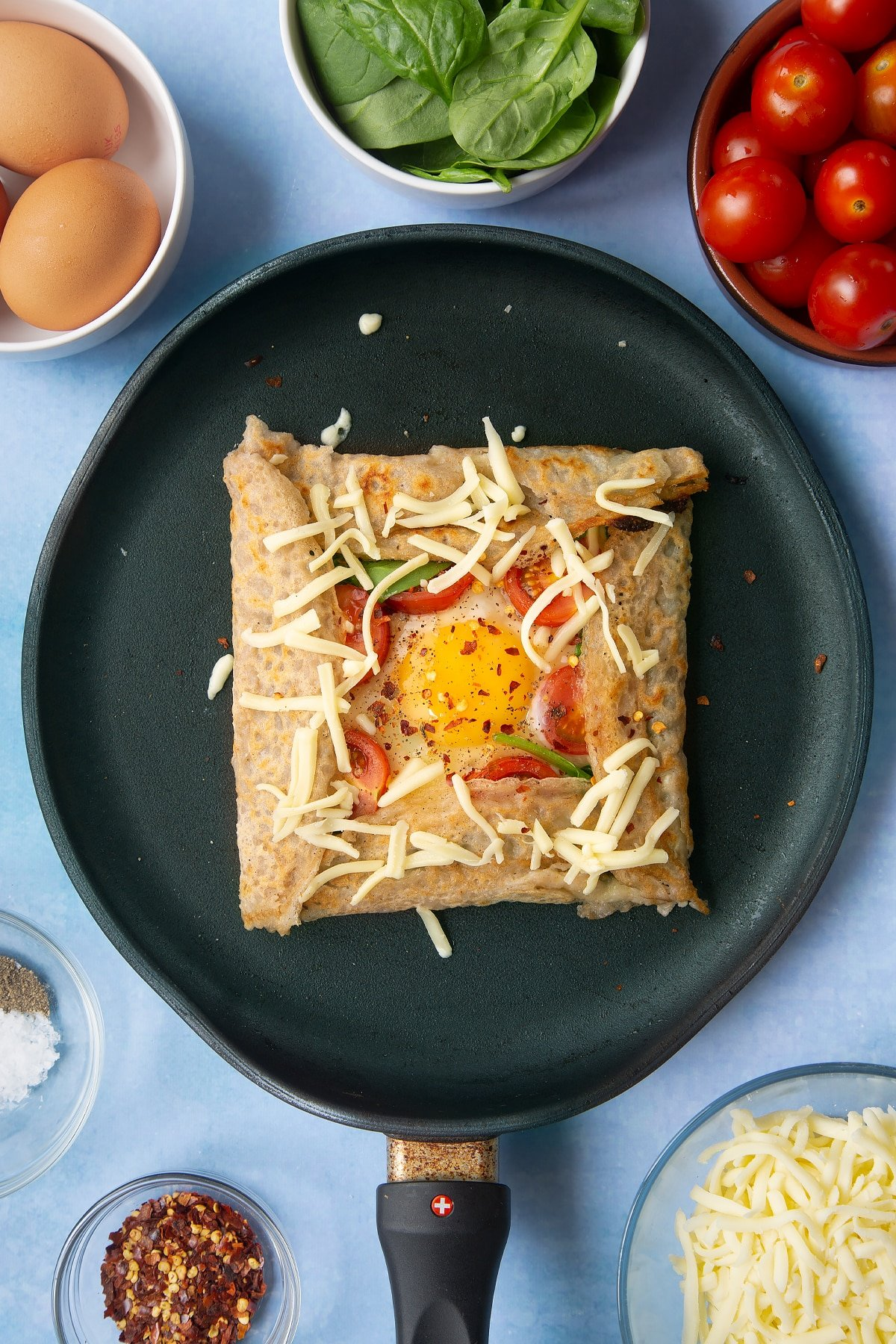 Folded buckwheat galette in a crepe pan, scattered with chilli flakes and grated cheese. Ingredients to make buckwheat galettes surround the pan.