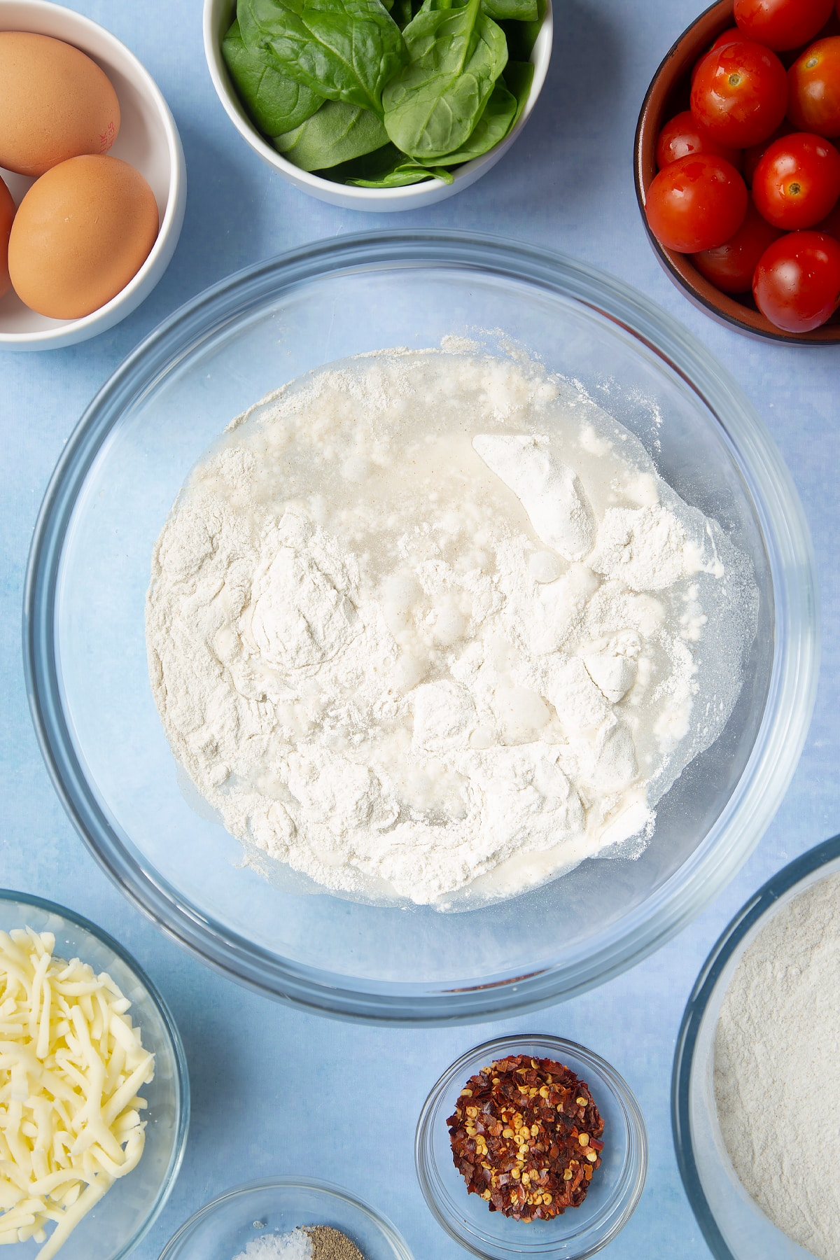 Buckwheat flour and water in a glass mixing bowl. Ingredients to make buckwheat galettes surround the bowl.