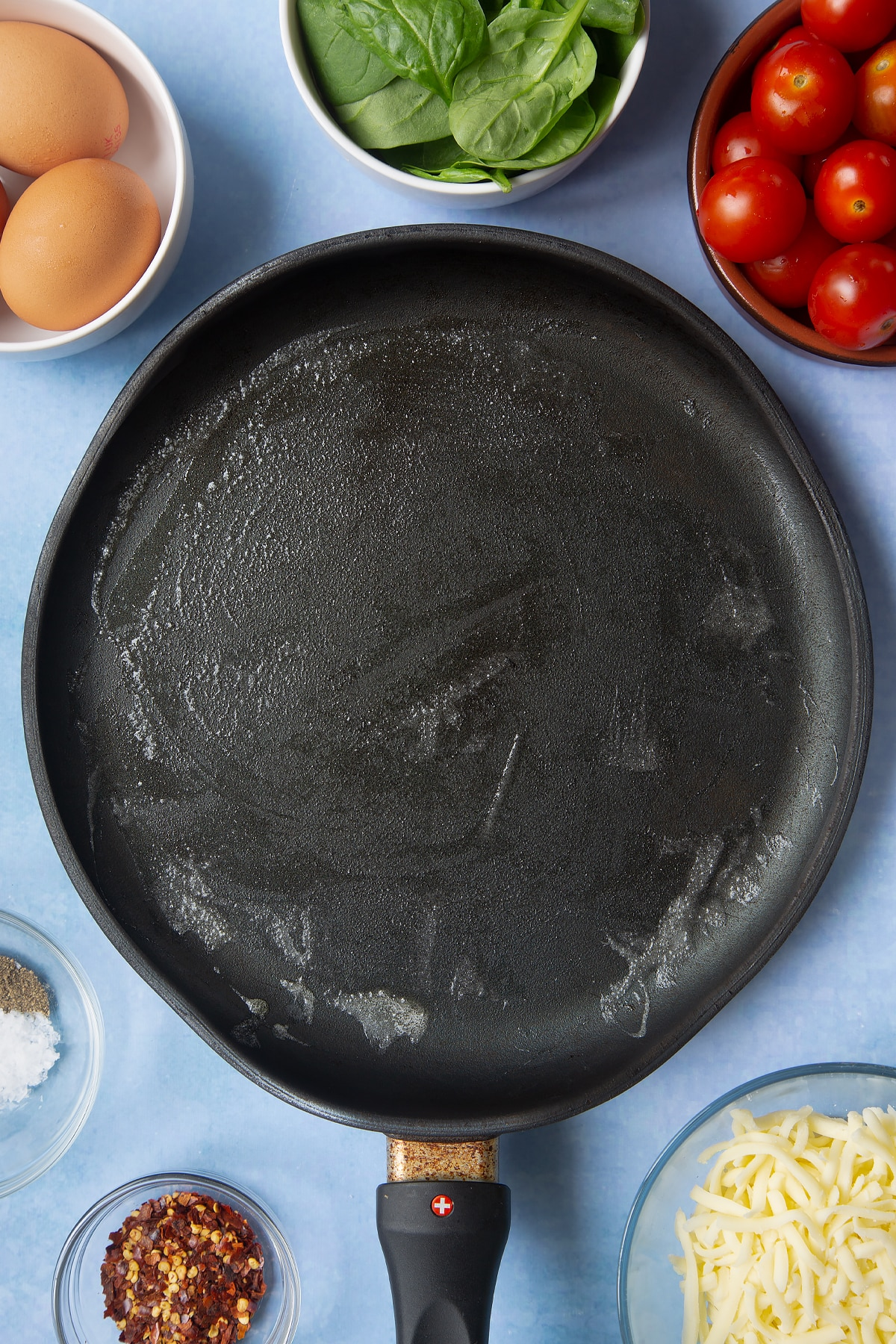 Butter melted in a crepe pan. Ingredients to make buckwheat galettes surround the pan.