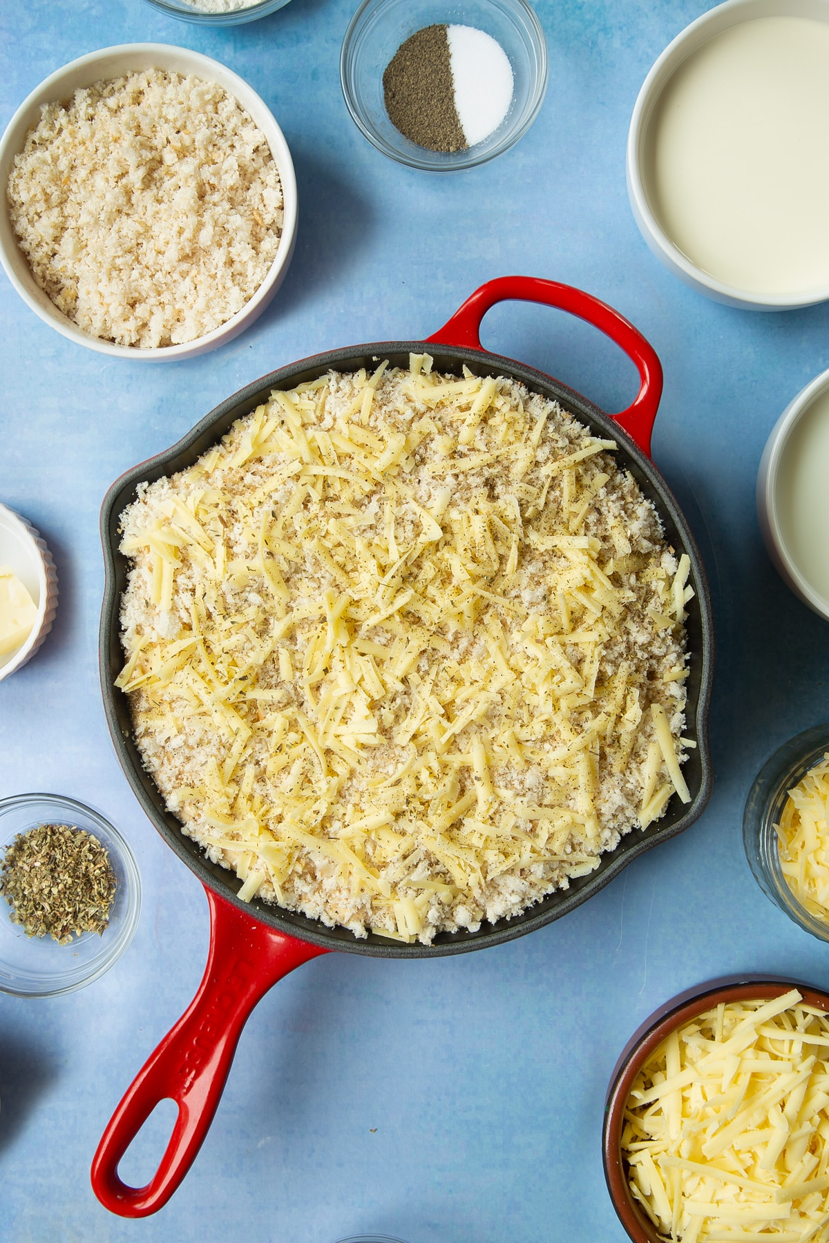 Spicy, cheesy, herby mac and cheese in a skillet with breadcrumbs, cheese and herbs on top. Ingredients to make garlic and herb mac and cheese surround the skillet.