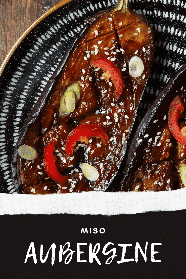 Close up of miso aubergine on a plate, topped with chilli, springs onions and sesame seeds. Caption reads: miso aubergine