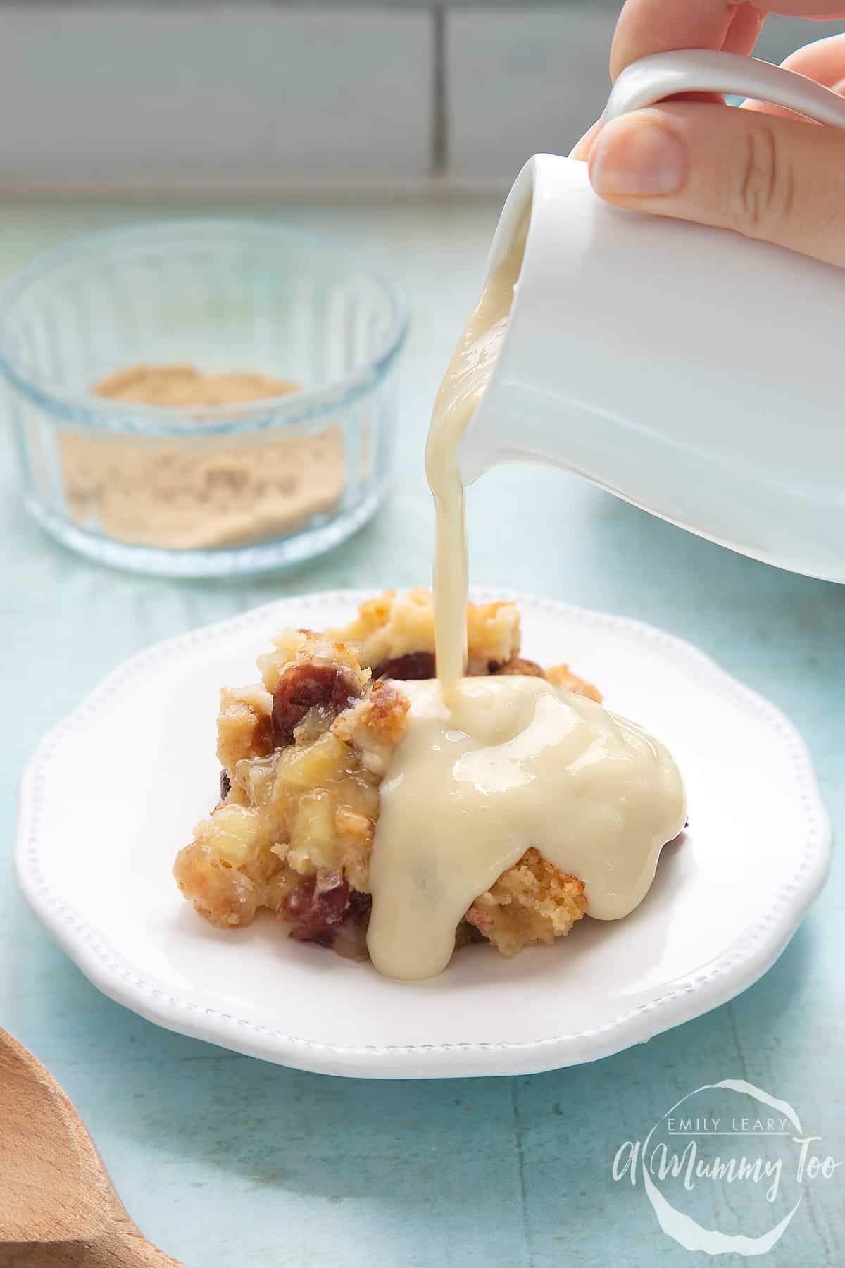 A berry crumble on a white plate covered with vegan custard being poured from a white jug.
