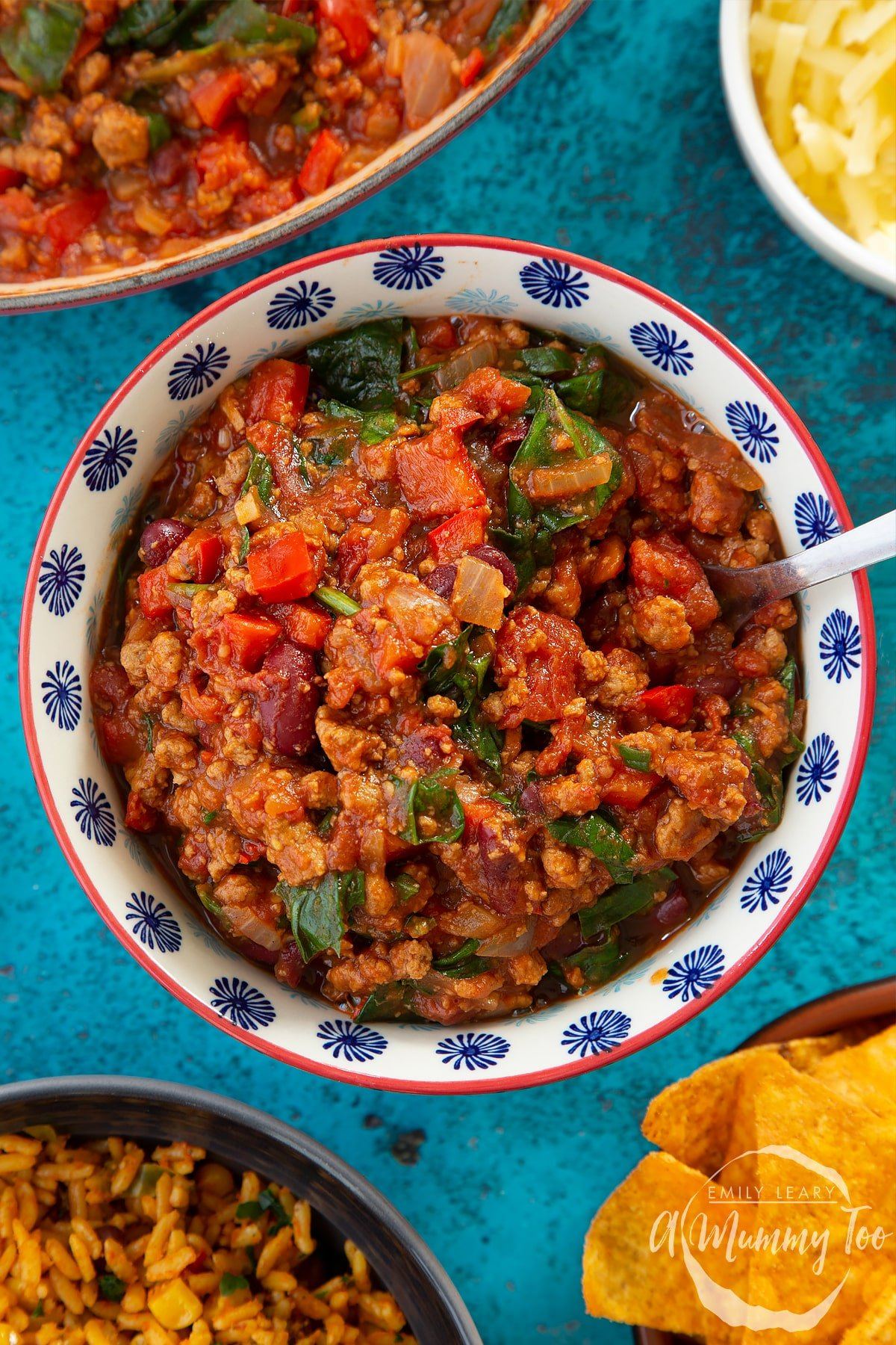 Vegetarian mince chilli in a bowl. A fork is in the bowl. Bowls containing tortilla chips, grated cheese and spicy rice are also shown.