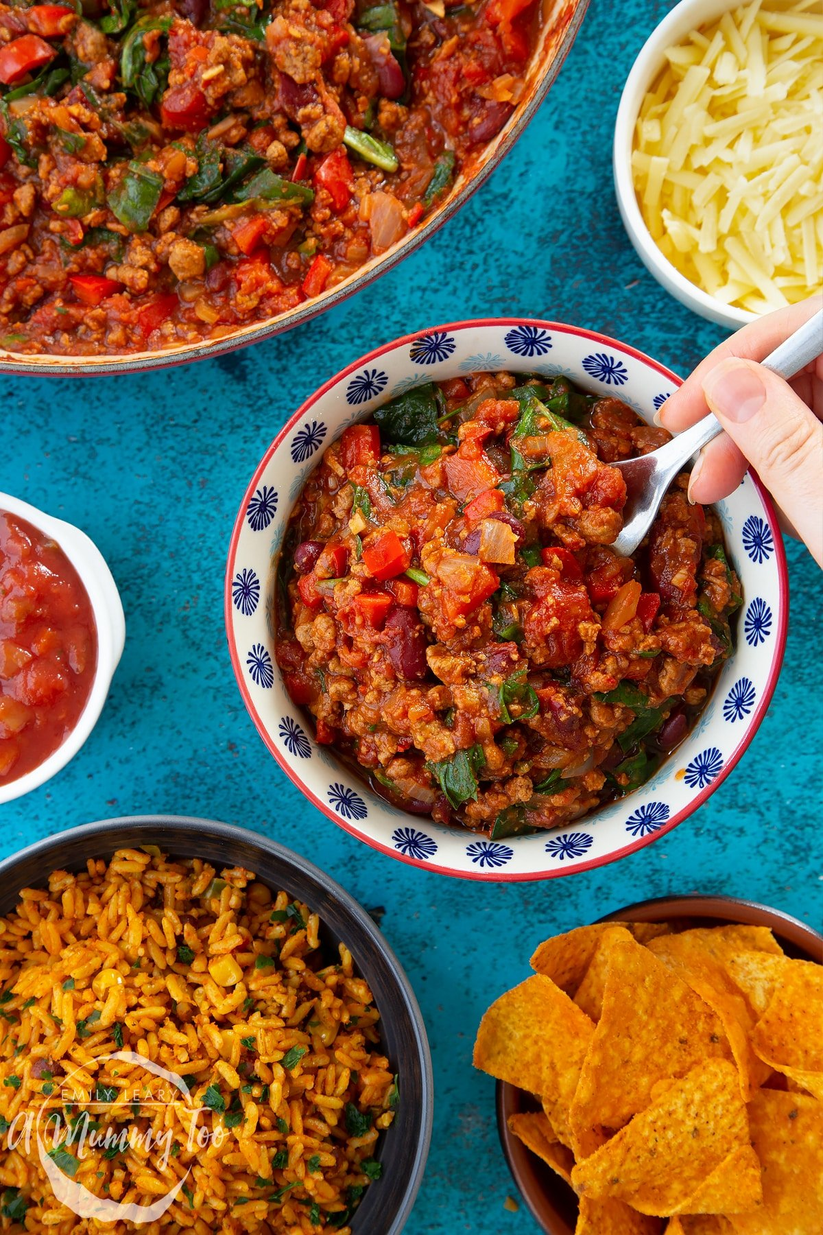 Vegetarian mince chilli in a bowl. A hand holding a fork delves into the chilli. Bowls containing tortilla chips, salsa, grated cheese and spicy rice are also shown.