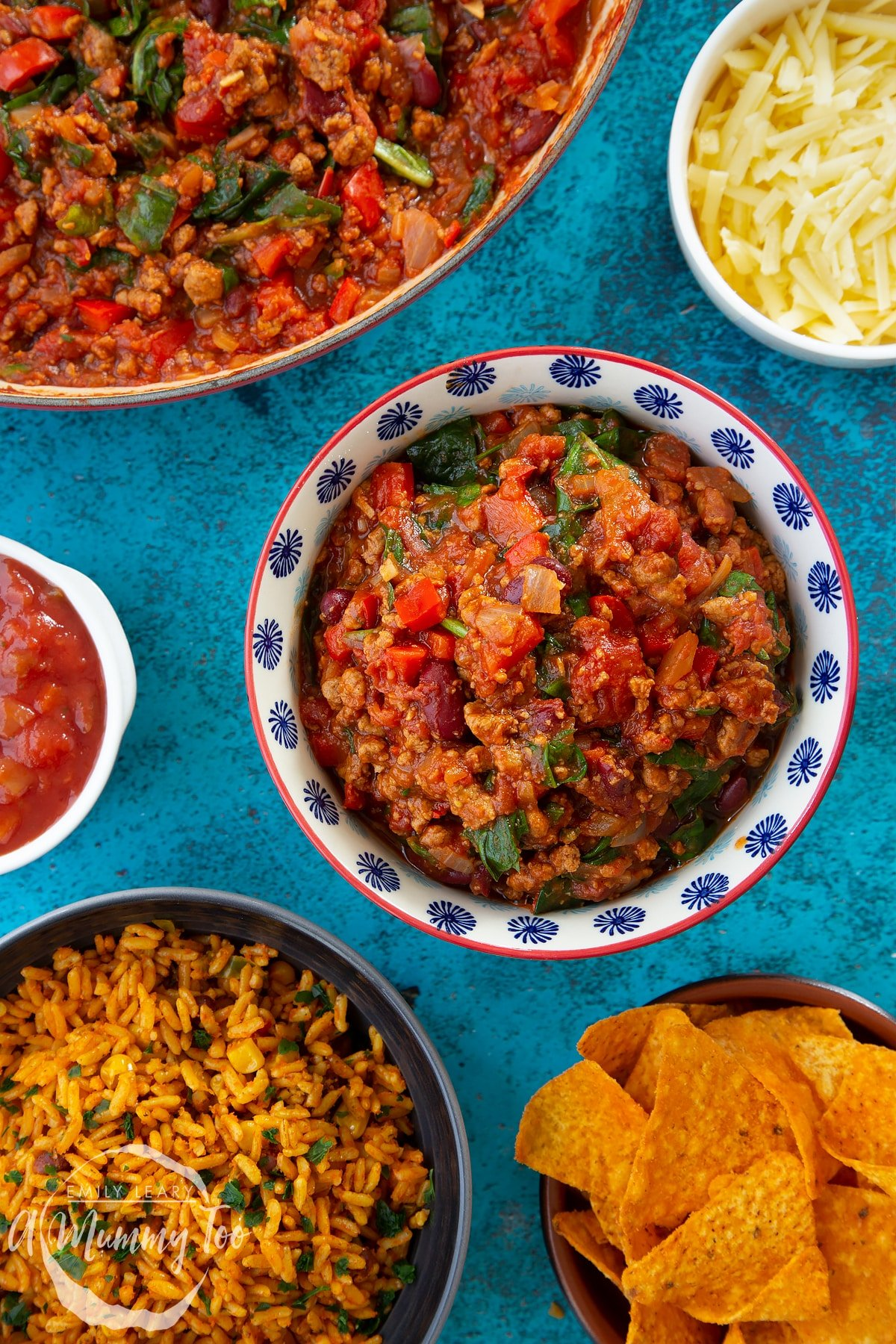 Vegetarian mince chilli in a bowl. Bowls containing tortilla chips, salsa, grated cheese and spicy rice are also shown.