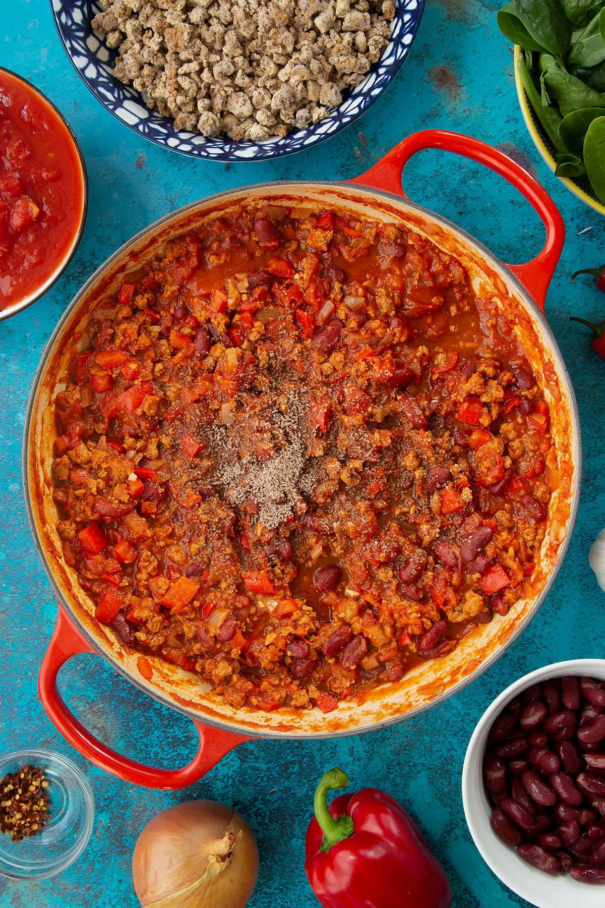 Vegetarian mince chilli in a pan with a pinch of salt and pepper on top. Ingredients to make vegetarian mince chilli surround the pan.