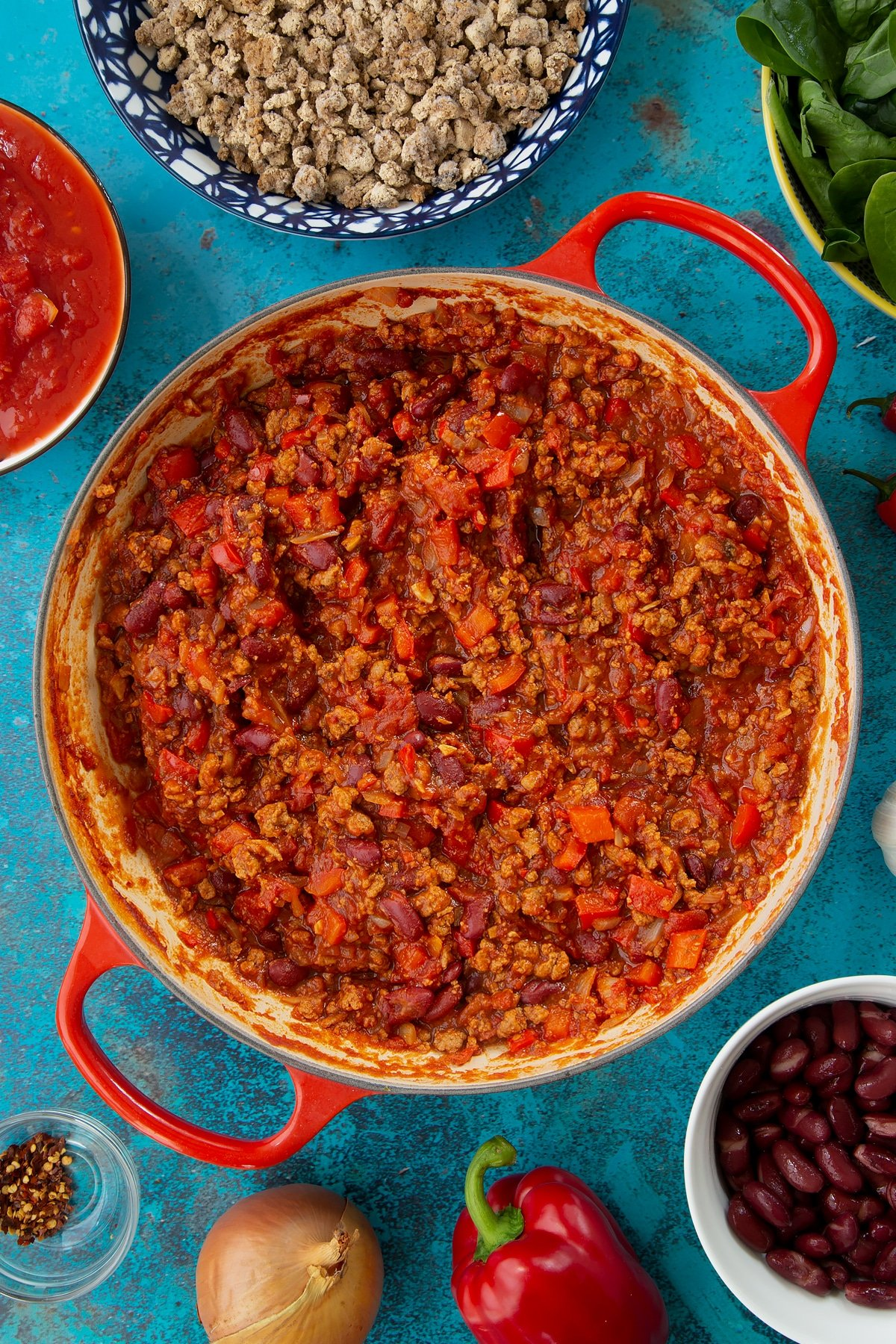 Vegetarian mince chilli in a pan, almost ready. Ingredients to make vegetarian mince chilli surround the pan.