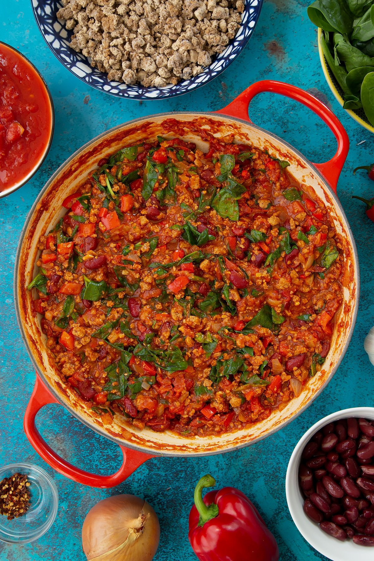 Vegetarian chilli in a pan, freshly cooked. Ingredients to make vegetarian mince chilli surround the pan.