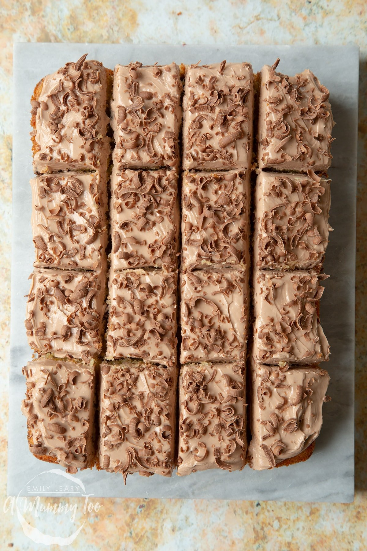 Freshly decorated chocolate chip tray bake on a marble board. The cake is cut into 16 pieces.