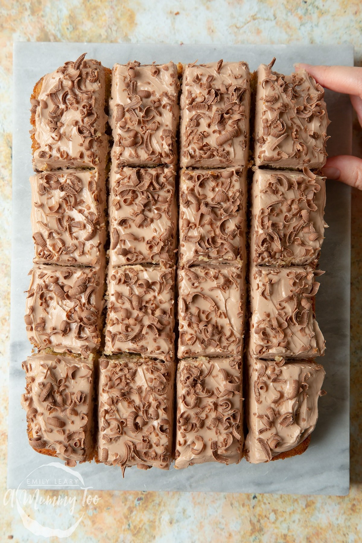 Chocolate chip tray bake on a marble board. A hand reaches to take a square.