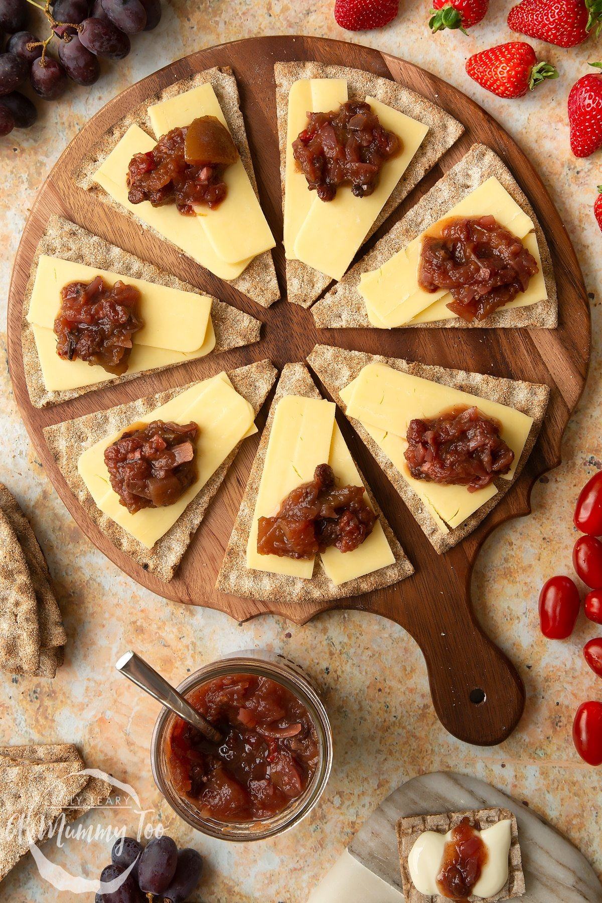 Triangular crackers topped with cheese slices and a fruit chutney recipe on a wooden board.