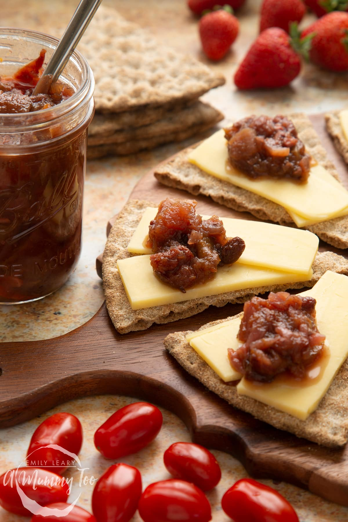 Triangular crackers topped with cheese slices and a fruit chutney recipe on a wooden board, next to a jar of chutney. Salad surrounds the board.