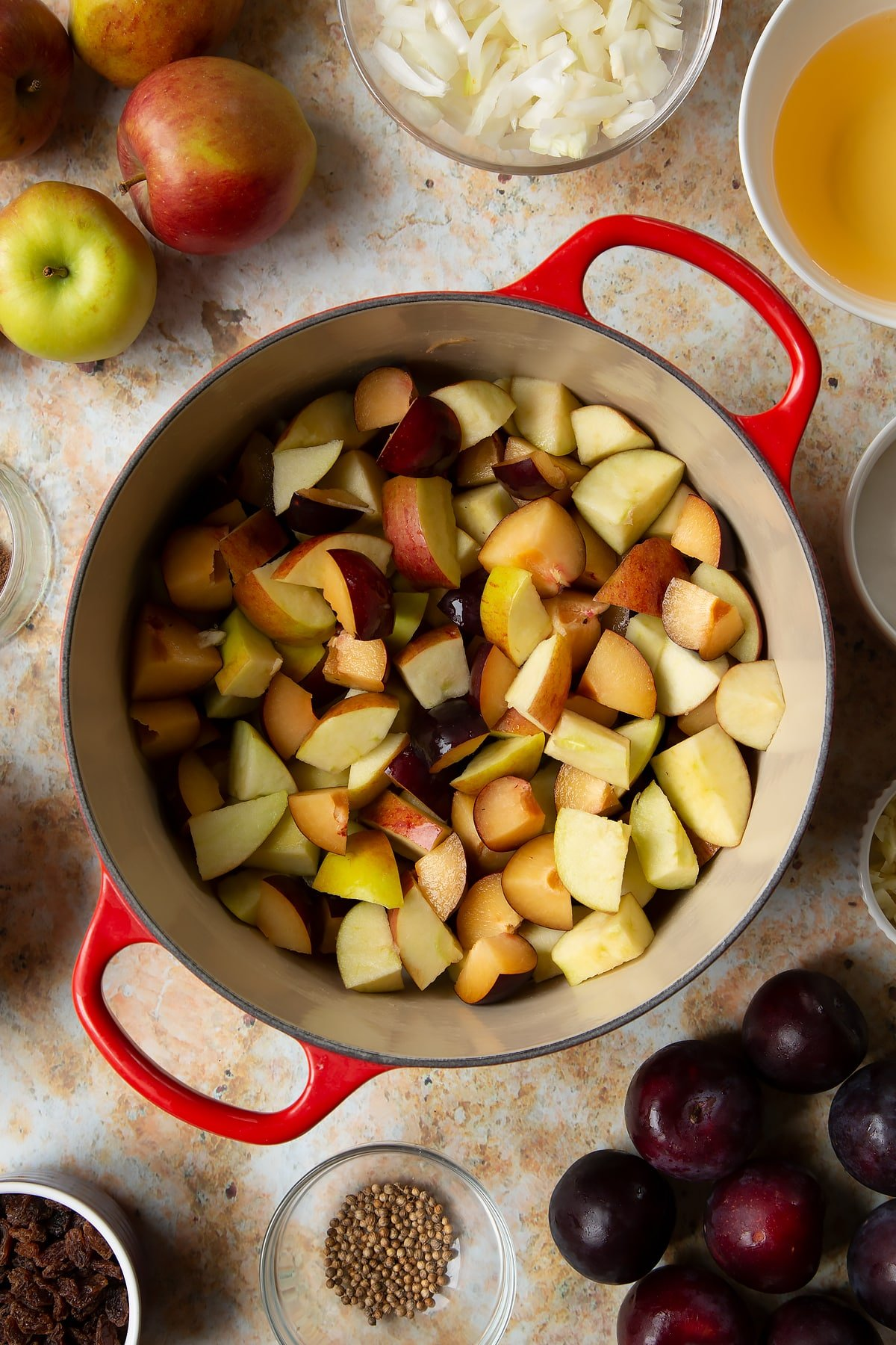 Chopped plums and apples in a large pan. Ingredients to make a fruit chutney recipe surround the pan.