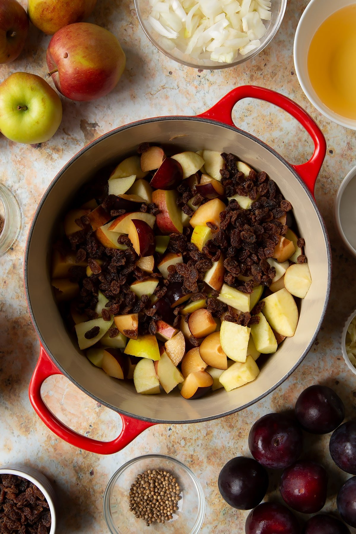 Chopped plums, apples and raisins in a large pan. Ingredients to make a fruit chutney recipe surround the pan.