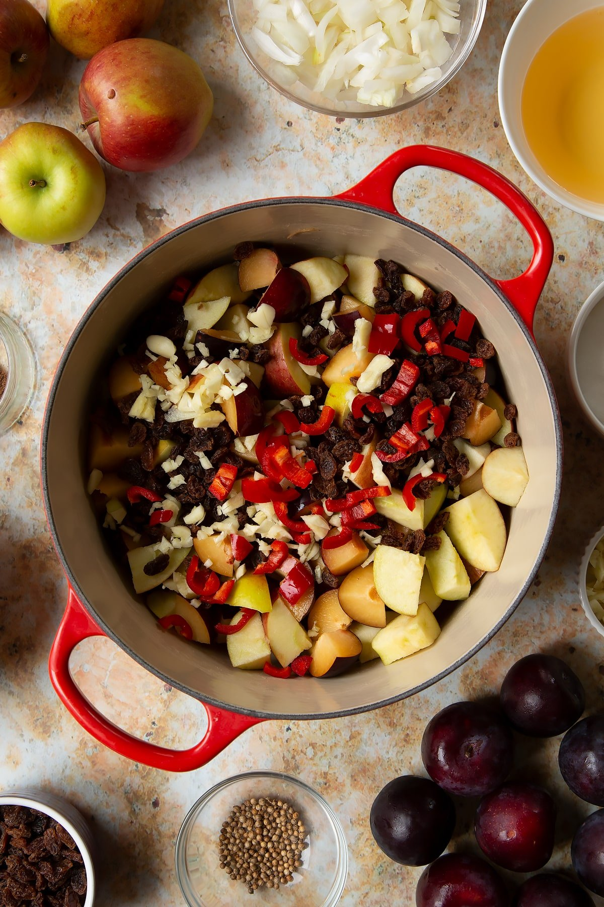 Chopped plums, apples, raisins, chilli and garlic in a large pan. Ingredients to make a fruit chutney recipe surround the pan.
