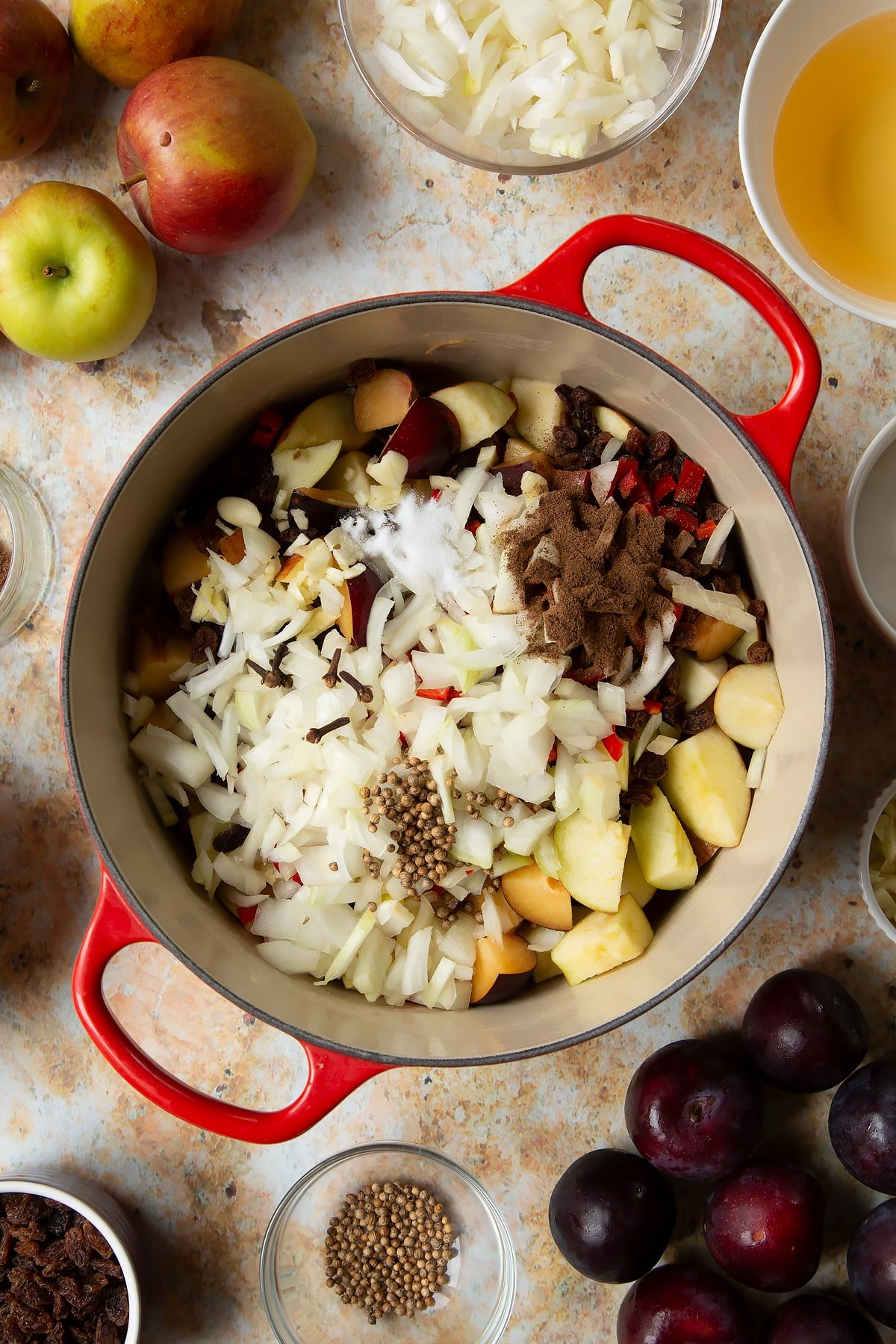 Chopped plums, apples, raisins, chilli, onion and garlic in a large pan. Ingredients to make a fruit chutney recipe surround the pan.