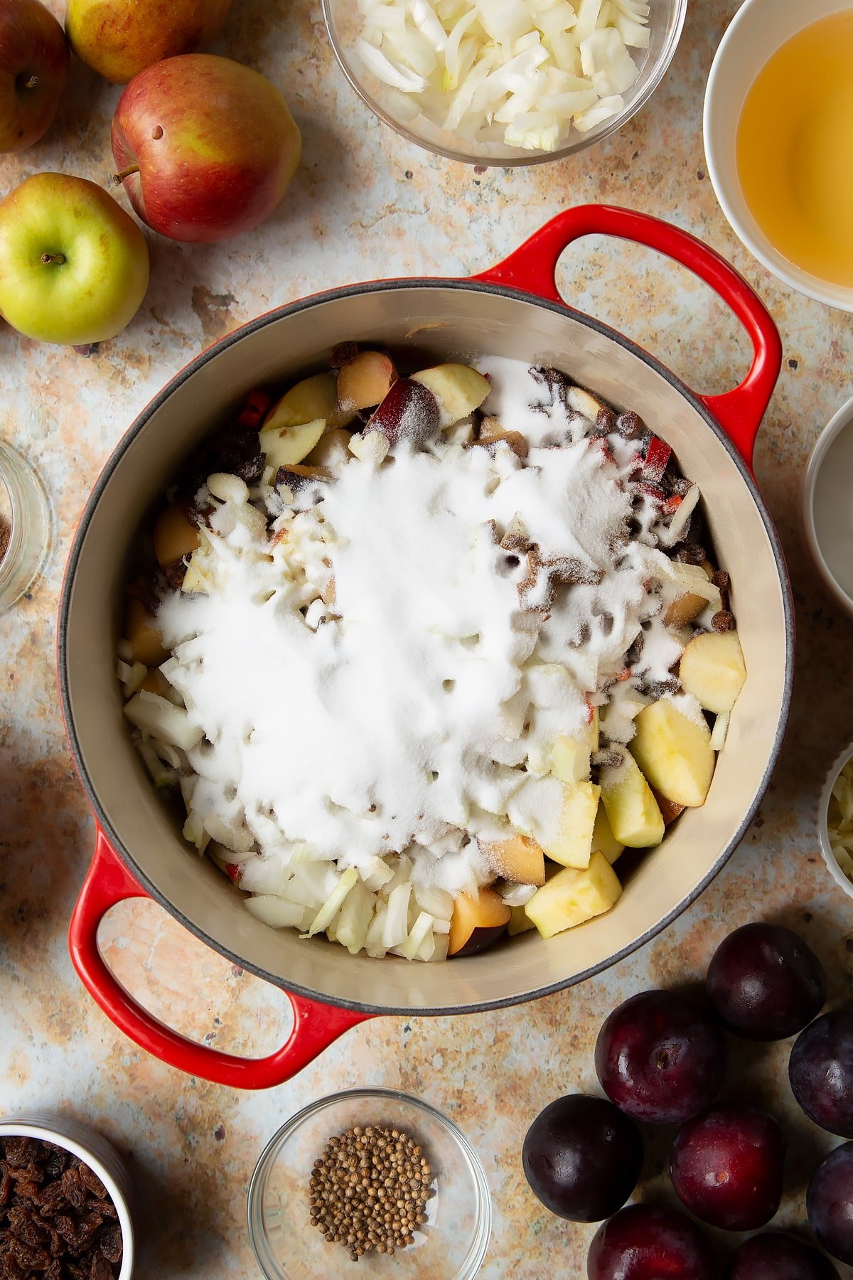 Chopped plums, apples, raisins, chilli, onion, garlic and sugar in a large pan. Ingredients to make a fruit chutney recipe surround the pan.