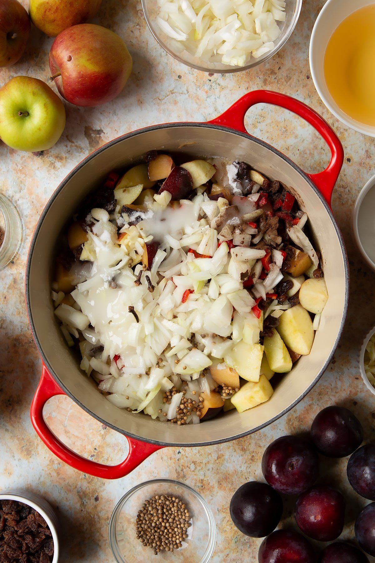 Chopped plums, apples, raisins, chilli, onion, garlic, sugar, vinegar and water in a large pan. Ingredients to make a fruit chutney recipe surround the pan.