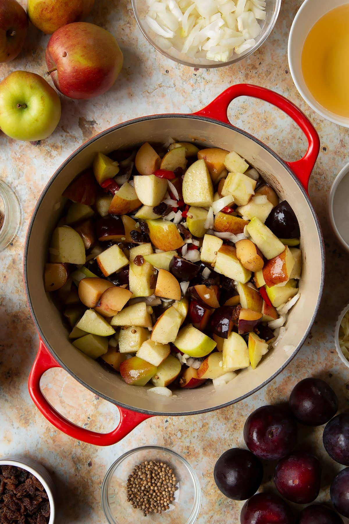 Fruit, spices, vinegar and water in a large pan. Ingredients to make a fruit chutney recipe surround the pan.