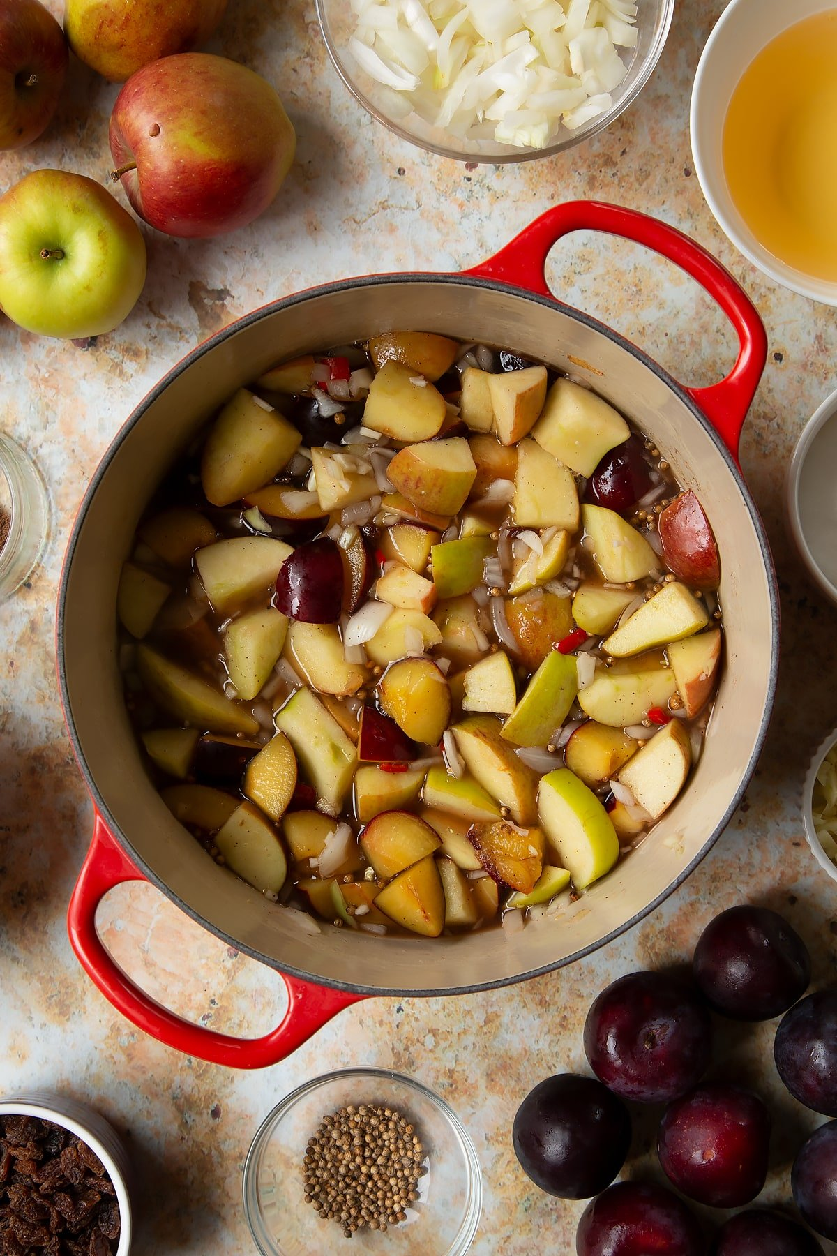 Hot fruit, spices, vinegar and water in a large pan. Ingredients to make a fruit chutney recipe surround the pan.