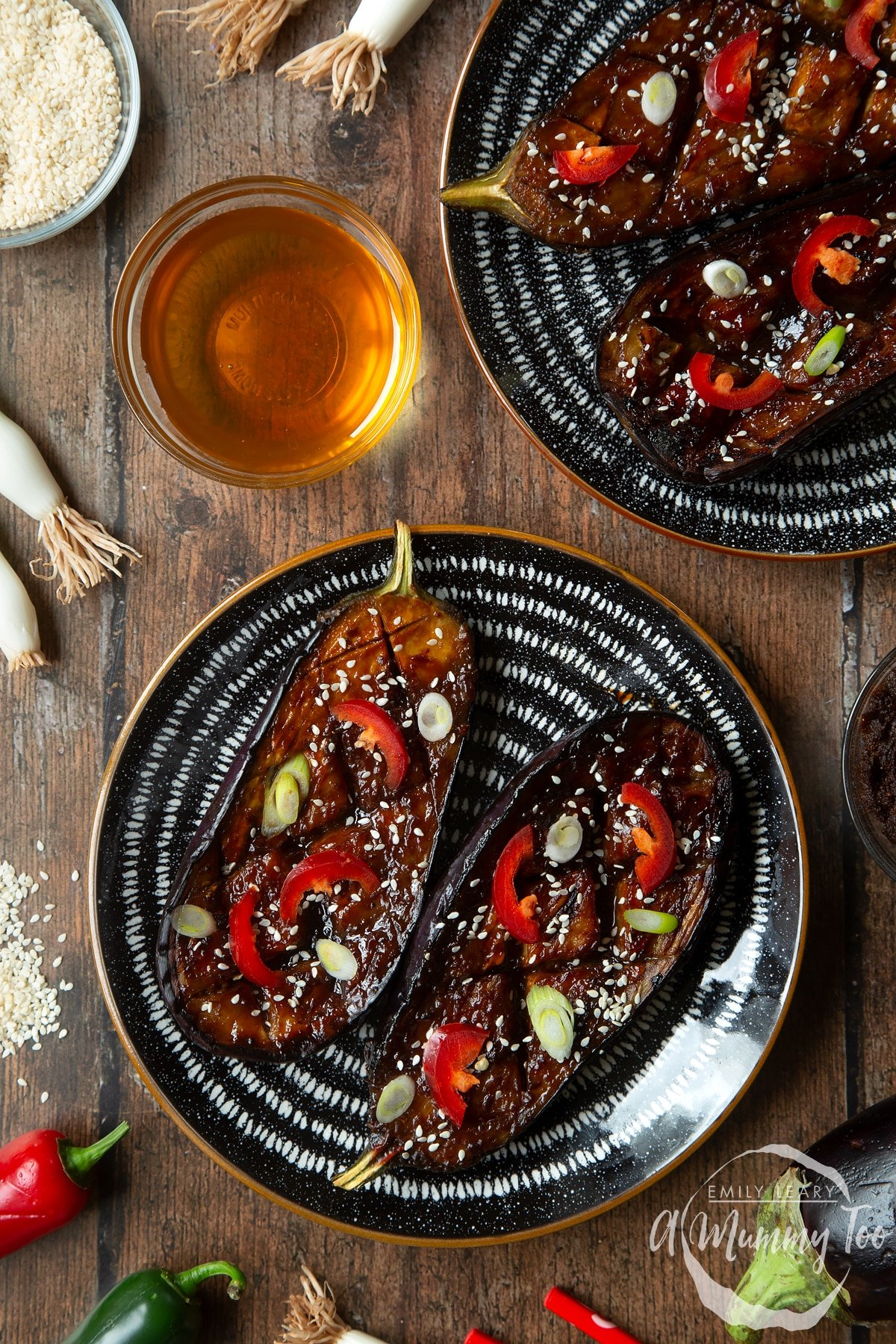 Two slices of miso aubergine on a plate, topped with chilli, spring onions and sesame seeds.