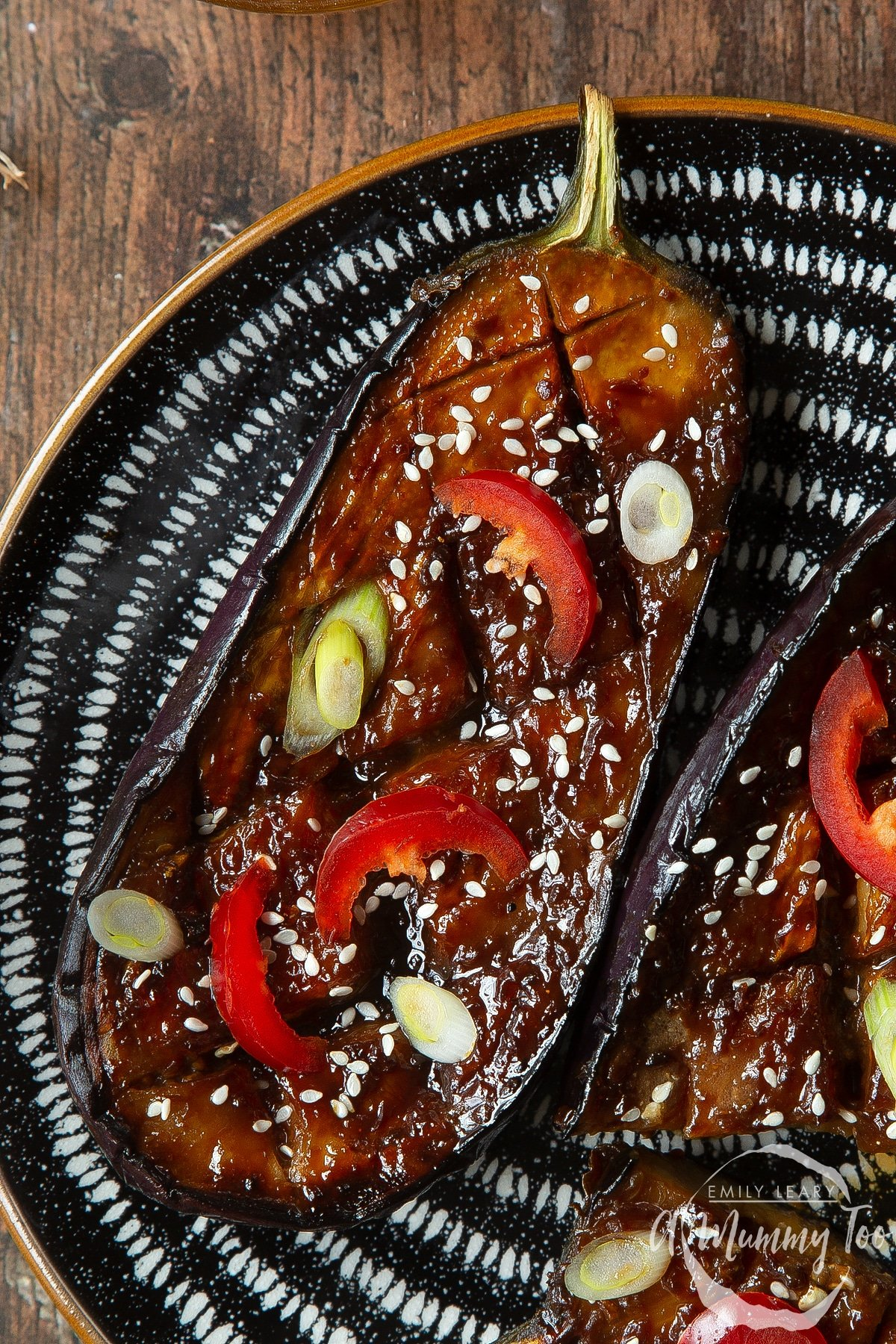 Close up of miso aubergine on a plate, topped with chilli, spring onions and sesame seeds.