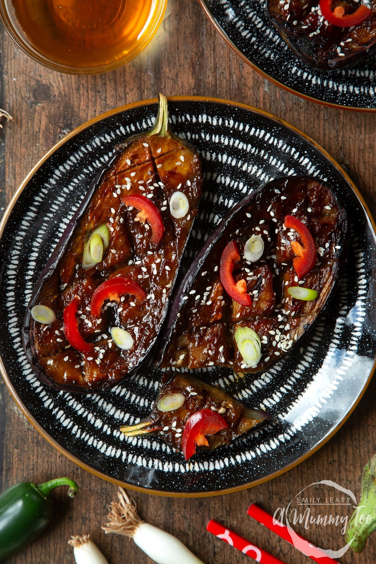 Two slices of miso aubergine on a plate, topped with chilli, springs onions and sesame seeds. One piece has been sliced.