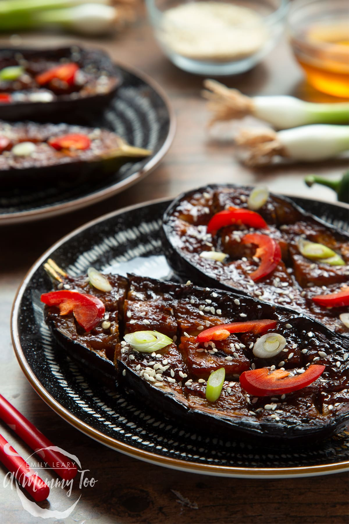 Miso aubergine on a plate, topped with chilli, springs onions and sesame seeds. Another plates shows in the background.