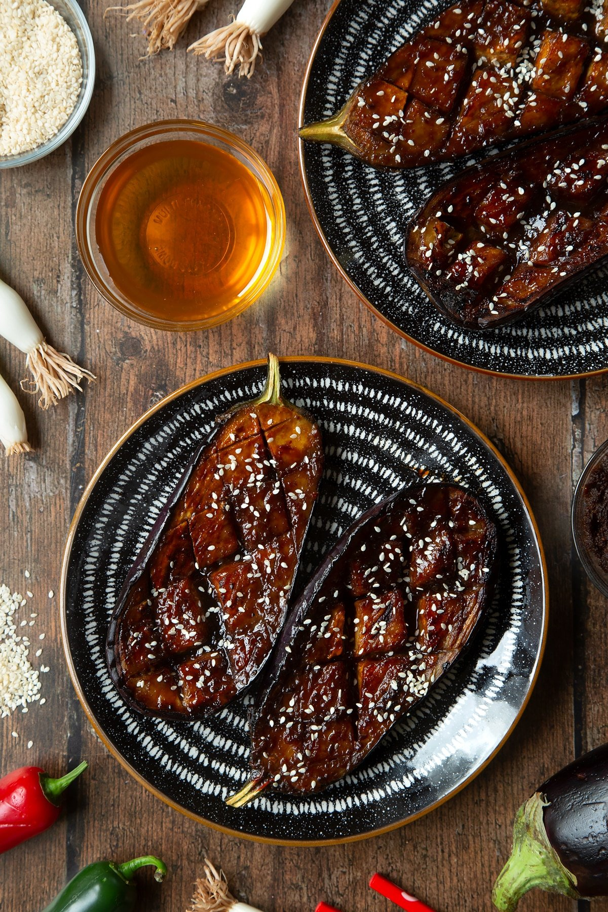 Aubergine halves with a miso glaze and sesame seeds on a plate. Ingredients to make miso aubergine surround the tray.
