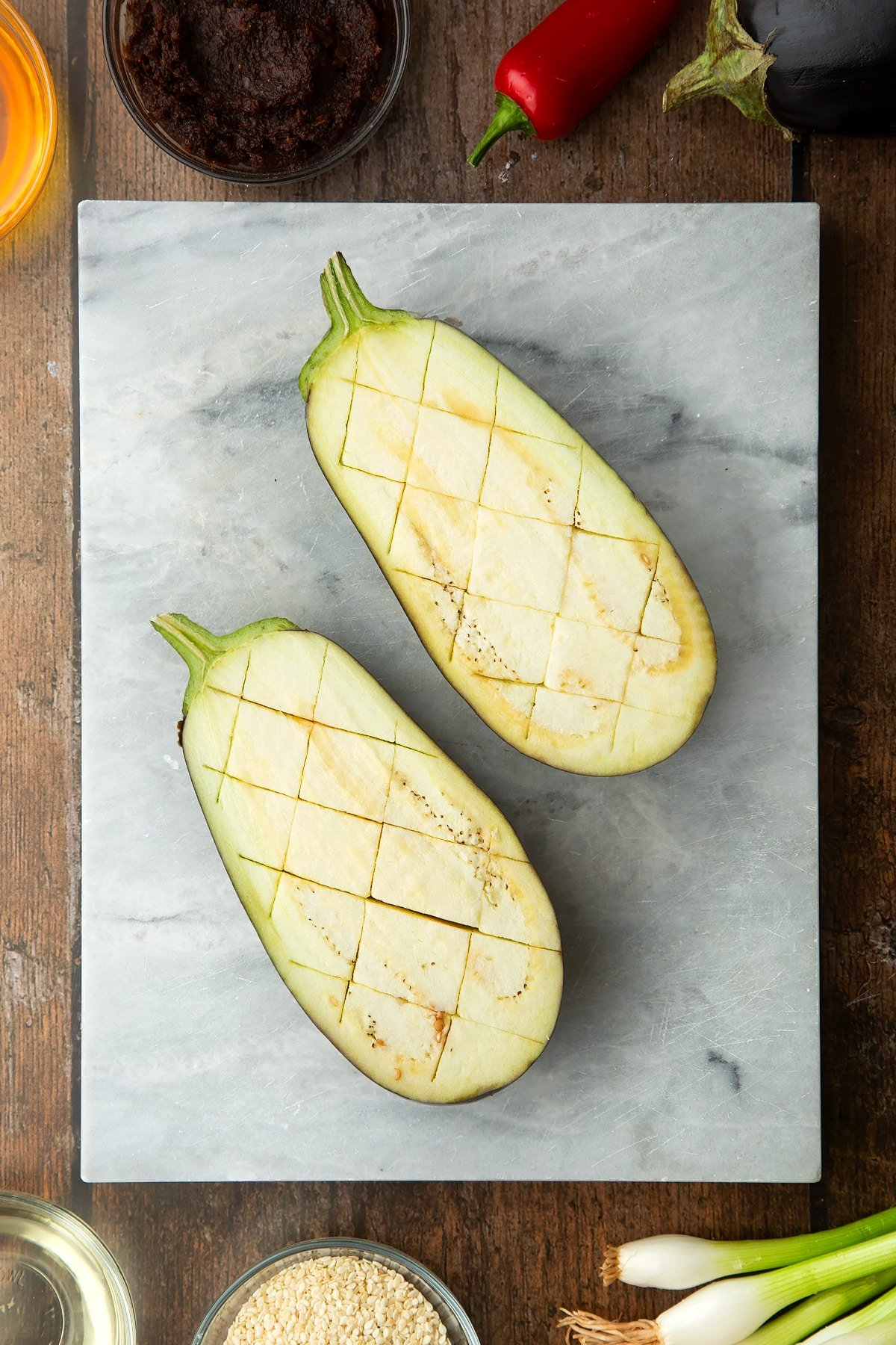 Aubergine sliced in half and scored on a board. Ingredients to make miso aubergine surround the board.