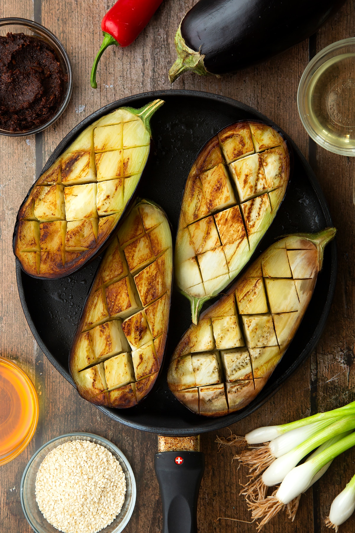 Scored and fried aubergine halves in a pan. Ingredients to make miso aubergine surround the pan.