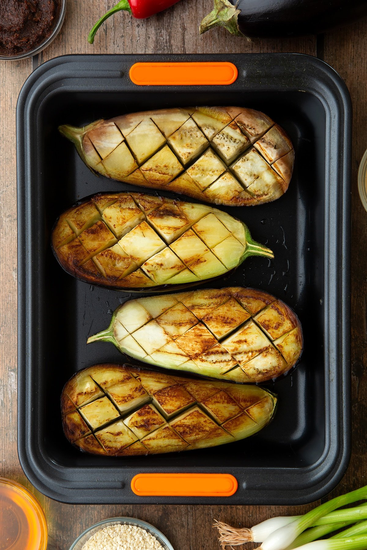 Scored and fried aubergine halves in a tray. Ingredients to make miso aubergine surround the tray.
