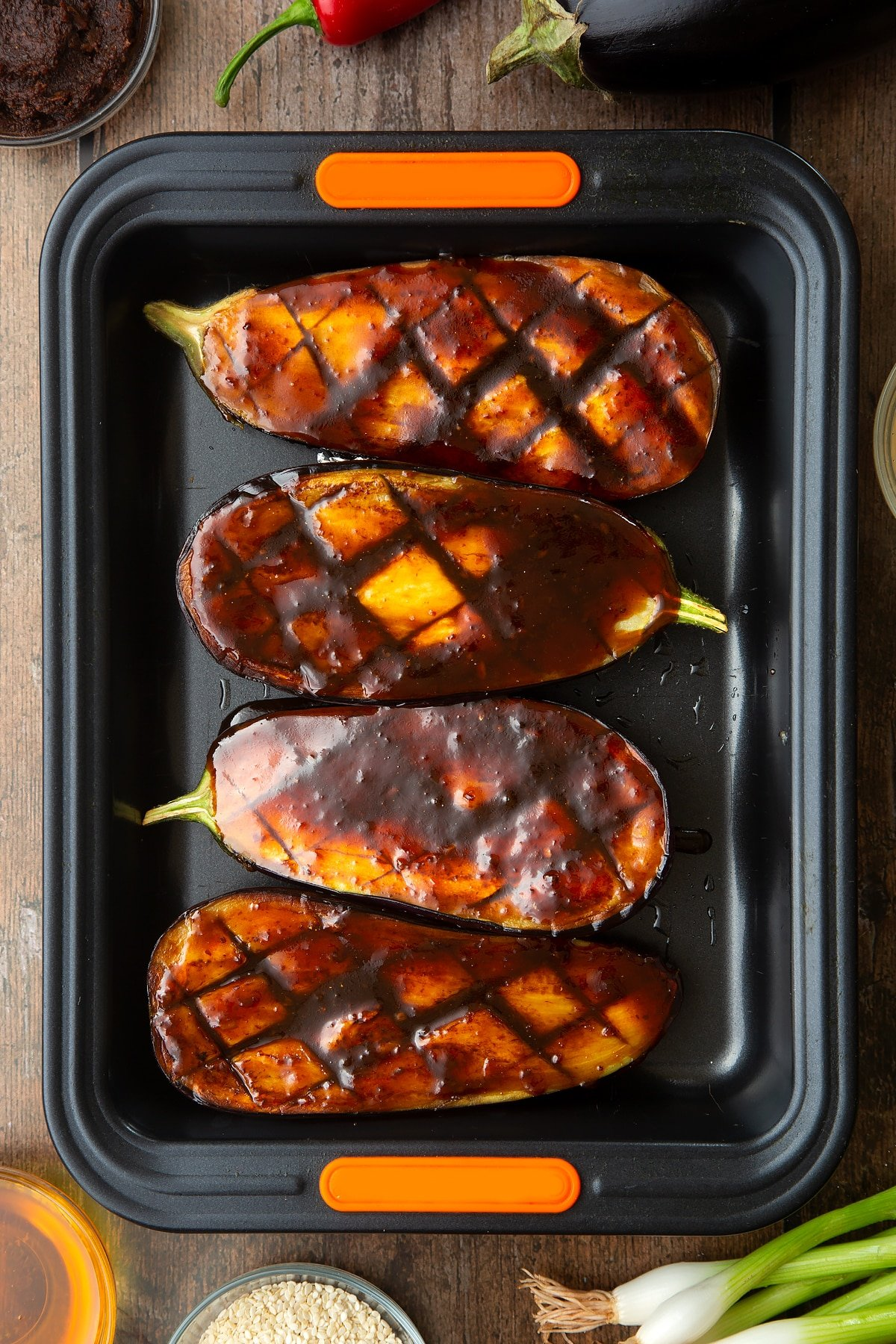 Scored and fried aubergine halves in a tray and covered with a miso glaze. Ingredients to make miso aubergine surround the tray.