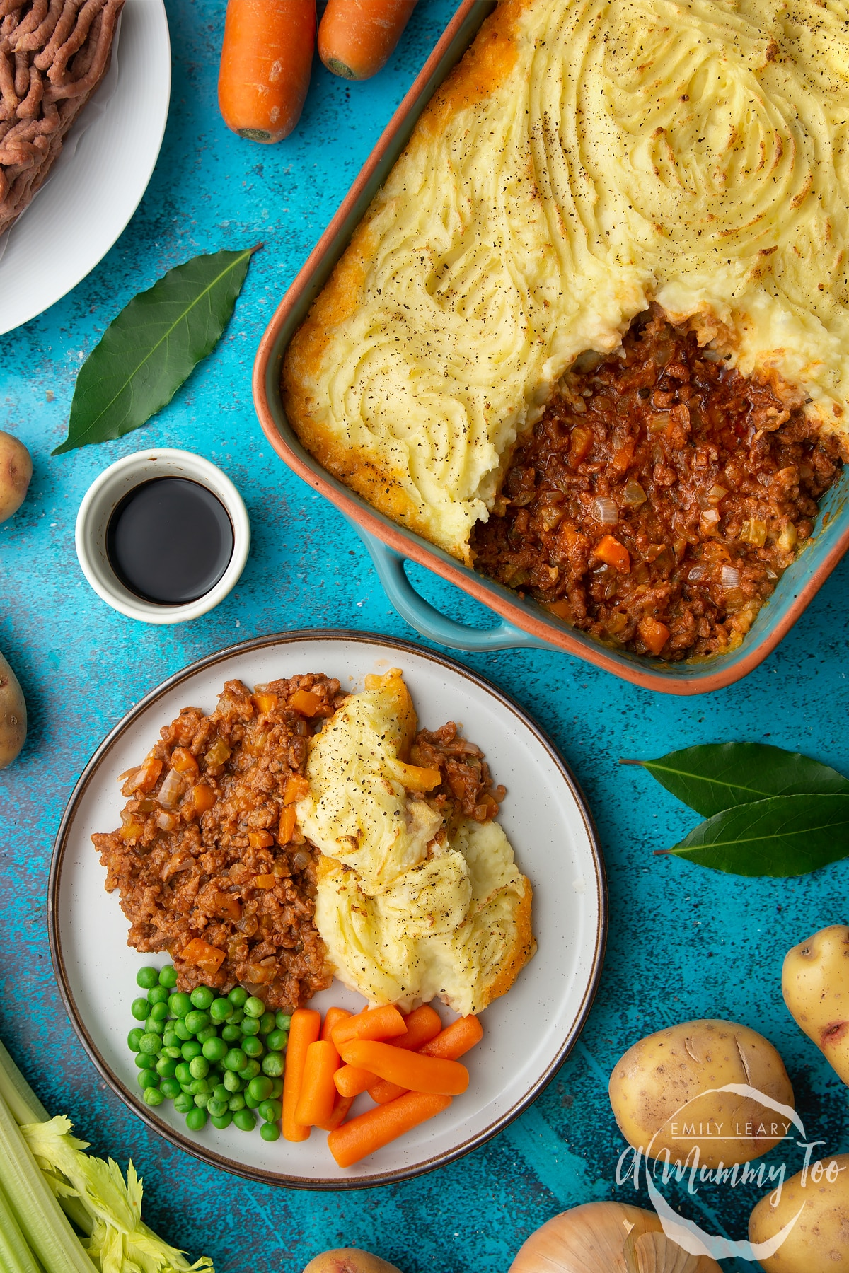 Vegan cottage pie served on a plate with peas and carrots. More pie is shown in its dish. Ingredients are scattered around.