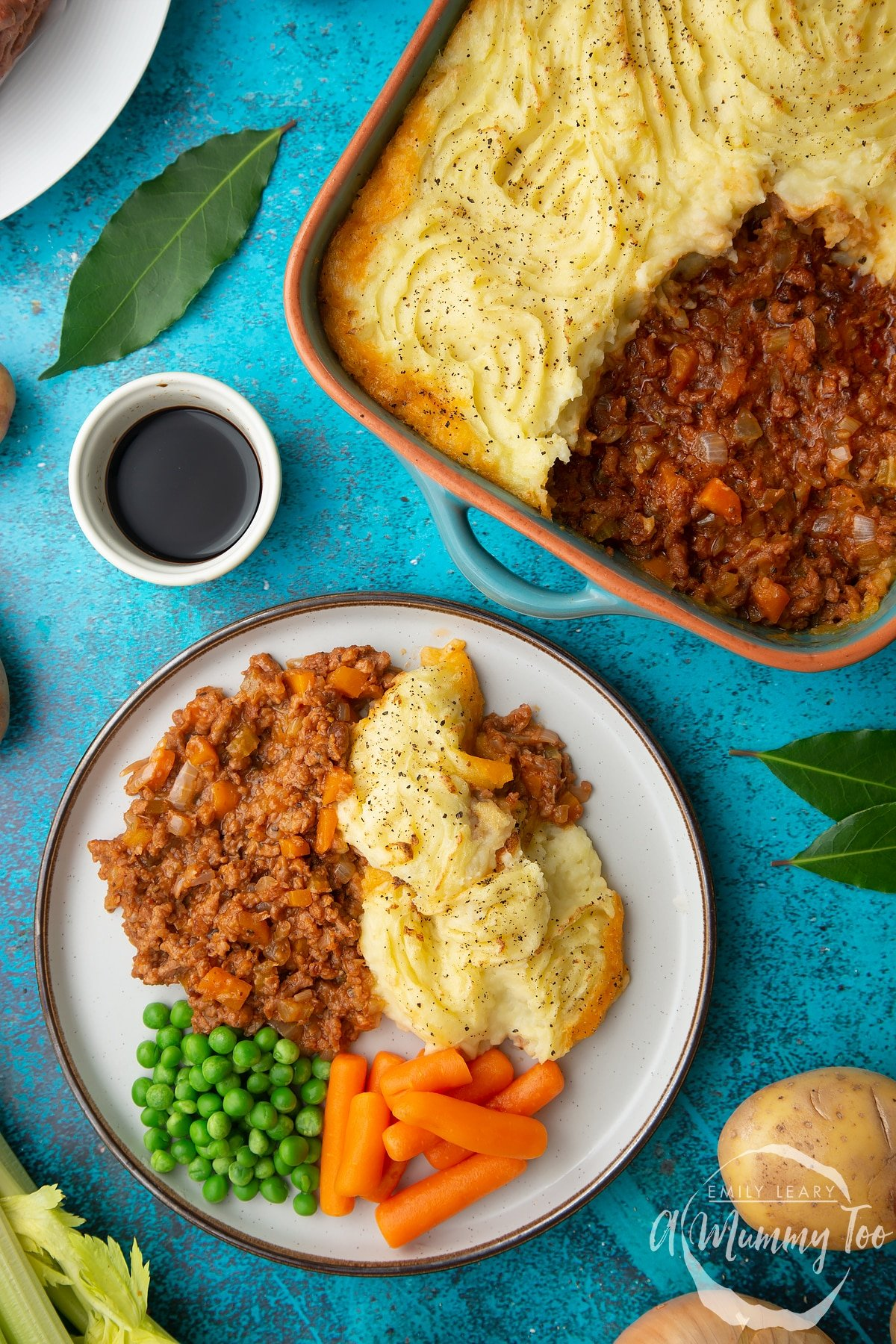 Vegan cottage pie served on a plate with peas and carrots. More pie is shown in a green roasting dish with an orange rim.