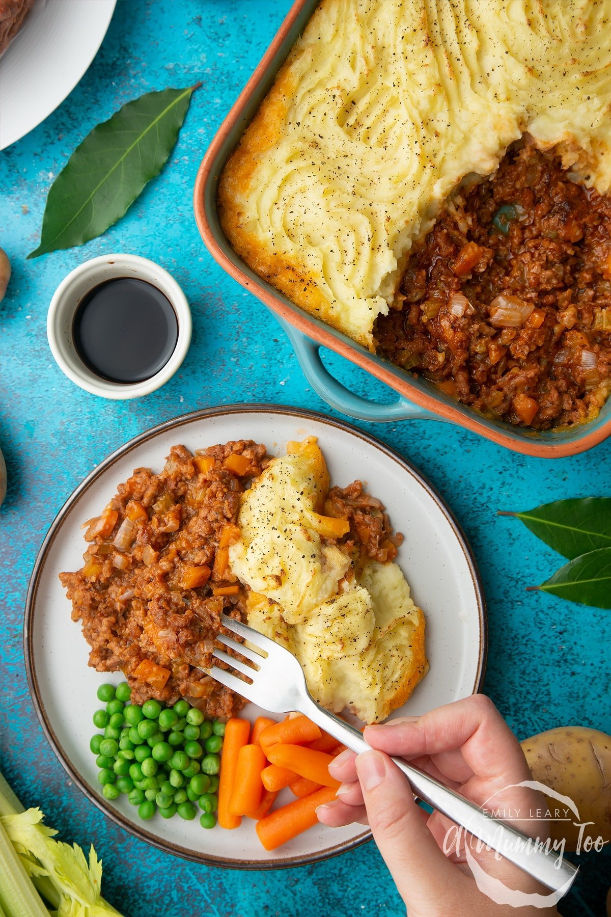 Vegan cottage pie served on a plate with peas and carrots. A hand holding a fork reaches in to take some. More pie is shown in its dish. Ingredients are scattered around.