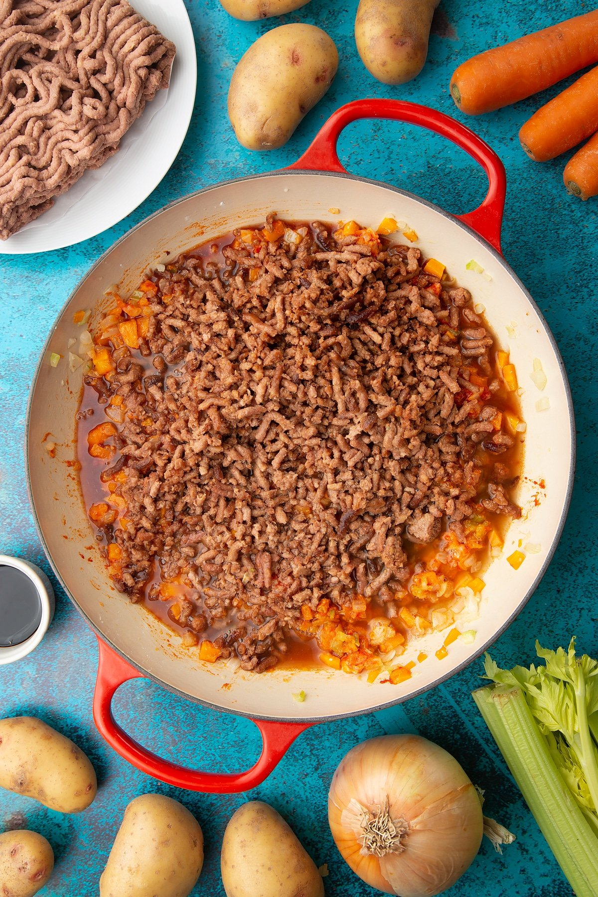 Fried onions, celery, carrots and garlic, flour, tomato puree, meat free mince, sage, wine and stock in a large pan. Ingredients to make vegan cottage pie surround the pan.