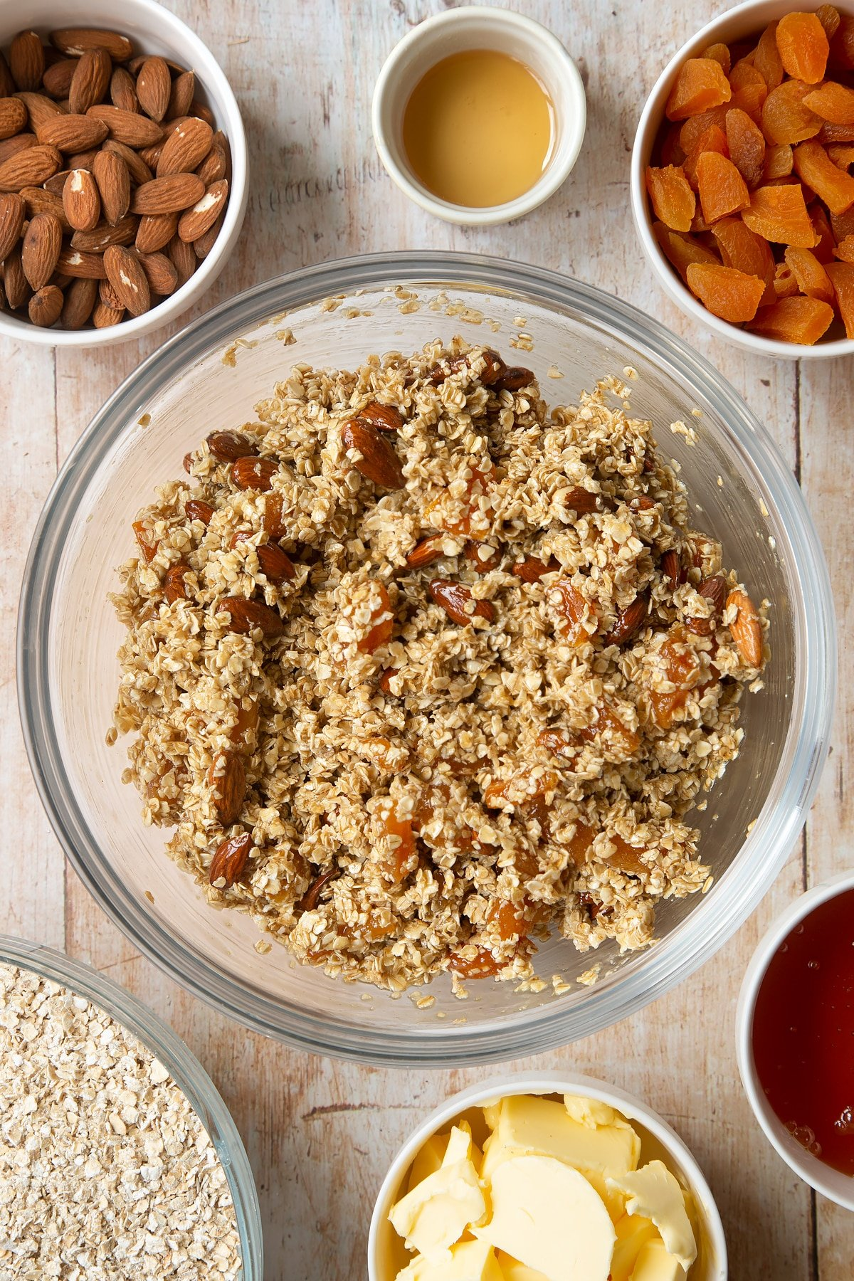 Overhead shot of oats, liquid mixture, apricots and nuts in a large clear bowl