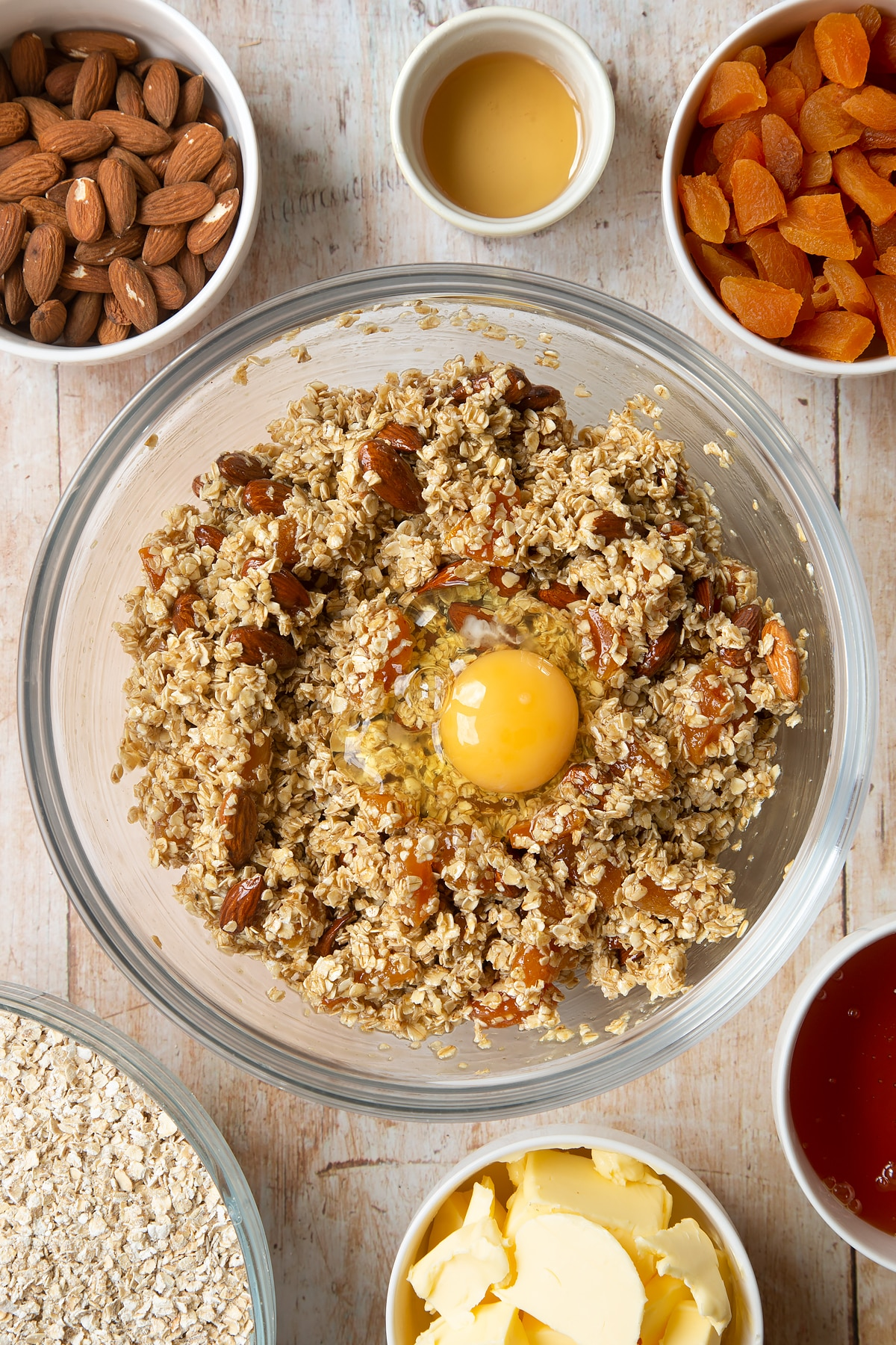 Overhead shot of oats, liquid mixture, apricots, nuts, and egg in a large clear bowl
