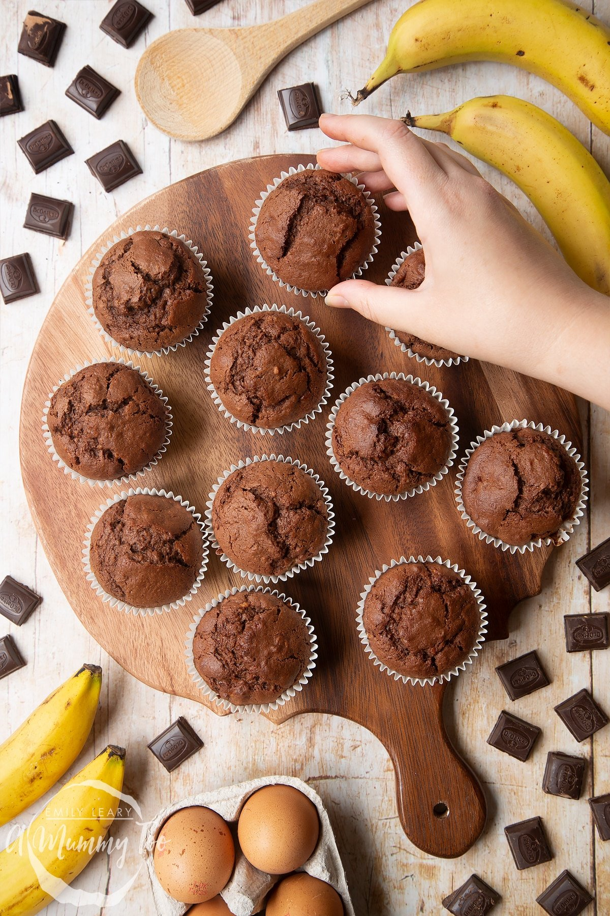 Overhead shot of a hand holding Banana and chocolate muffins served on a wooden plate with a mummy too logo in the lower-right corner
