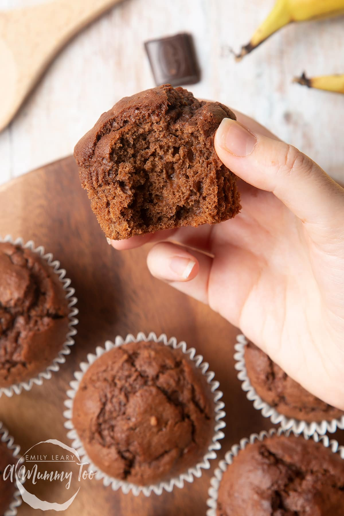 front angle shot of a hand holding a half eaten banana and chocolate muffins with a mummy too logo in the lower-left corner