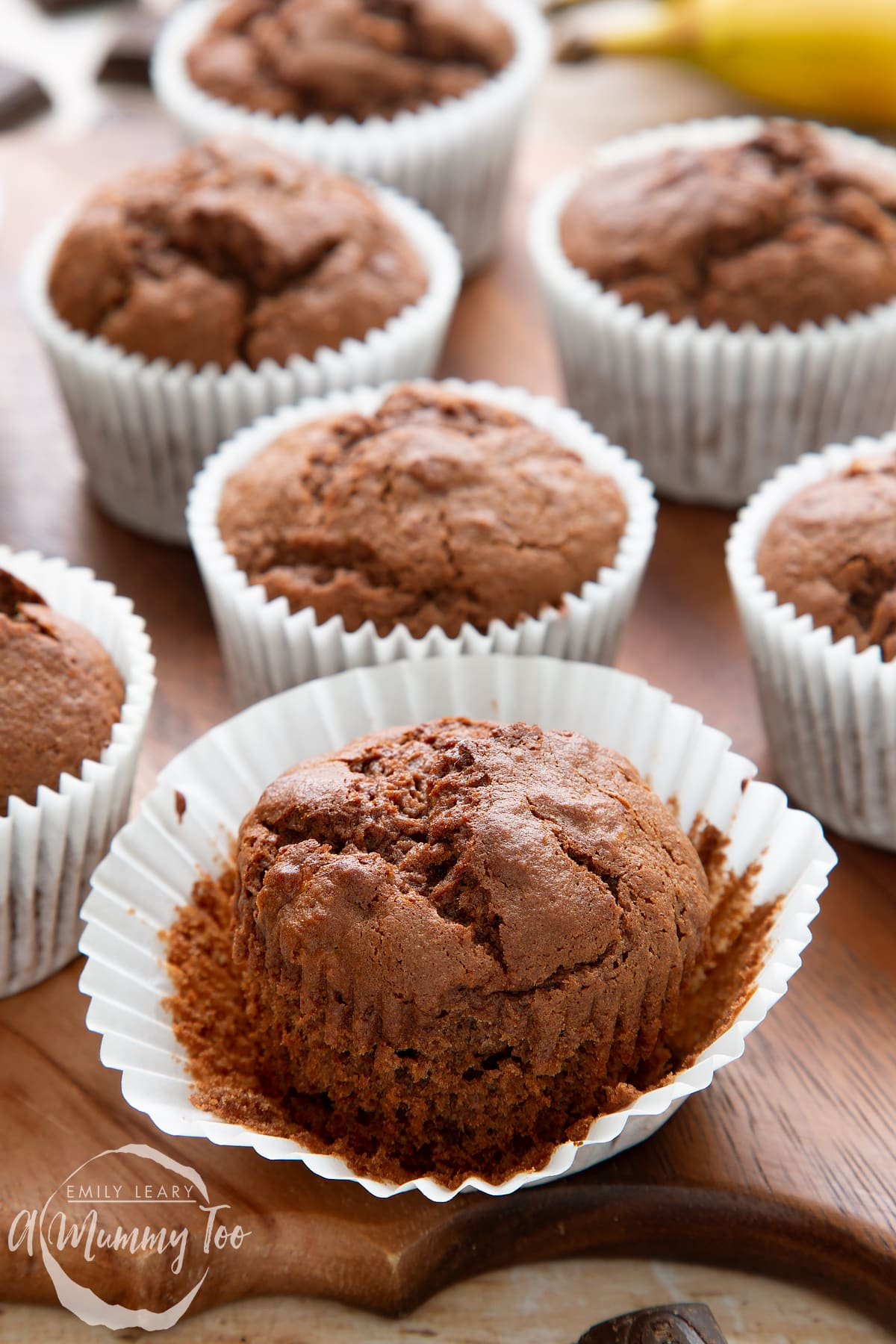 Front angle shot of banana and chocolate muffins with opened muffin cases served in a wooden plate