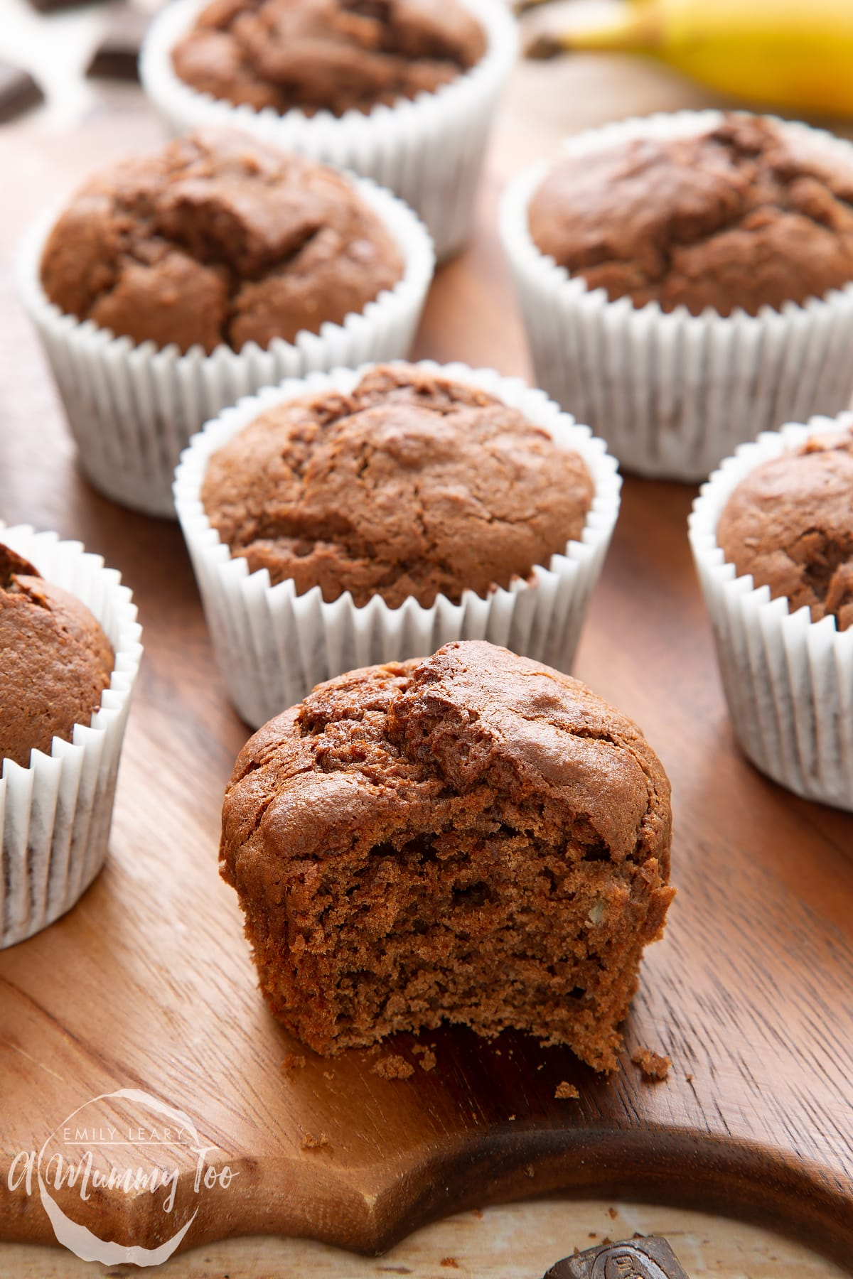 front angle shot of a half eaten banana and chocolate muffins with a mummy too logo in the lower-left corner