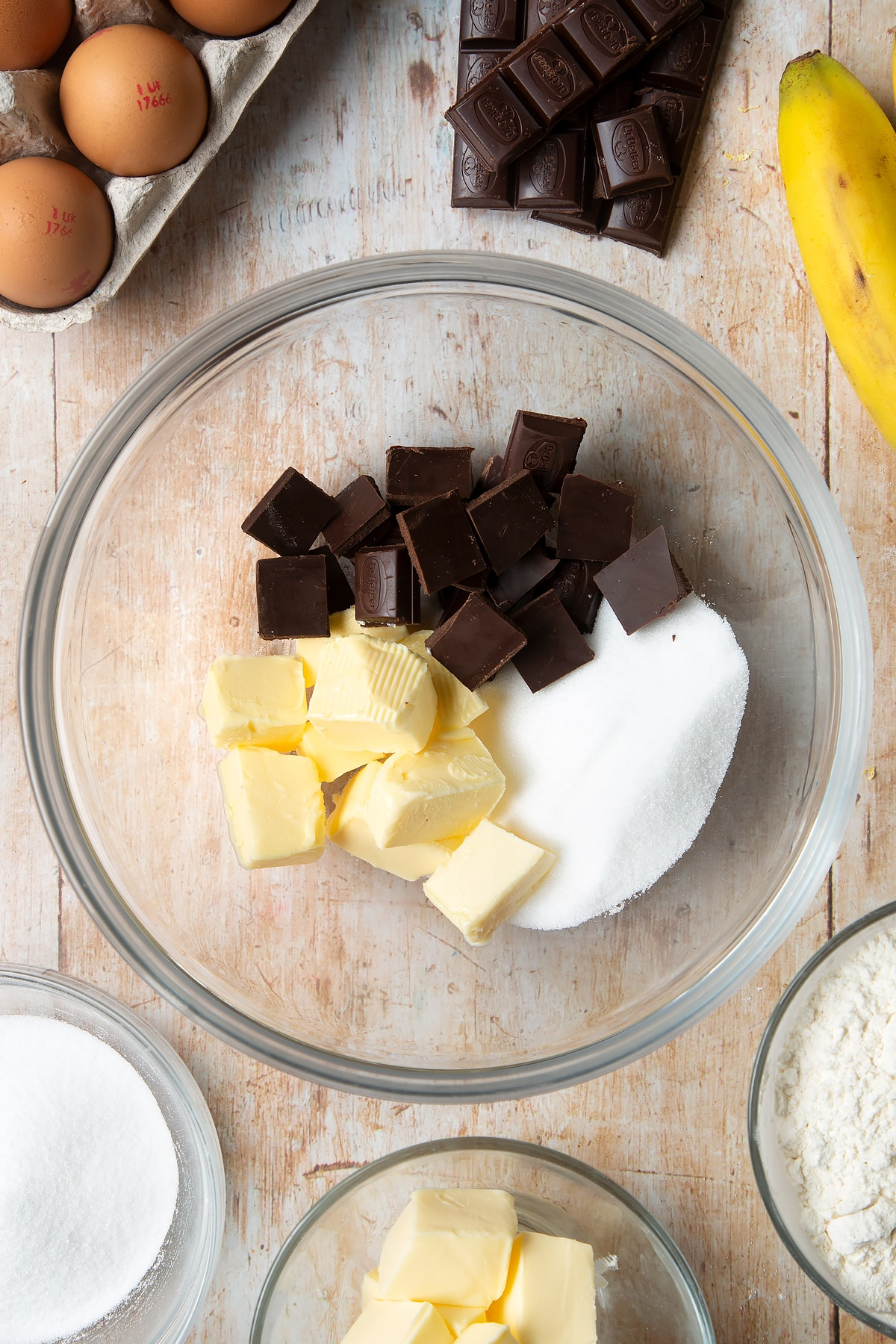 Overhead shot of butter, sugar, and chocolate in a large clear bowl