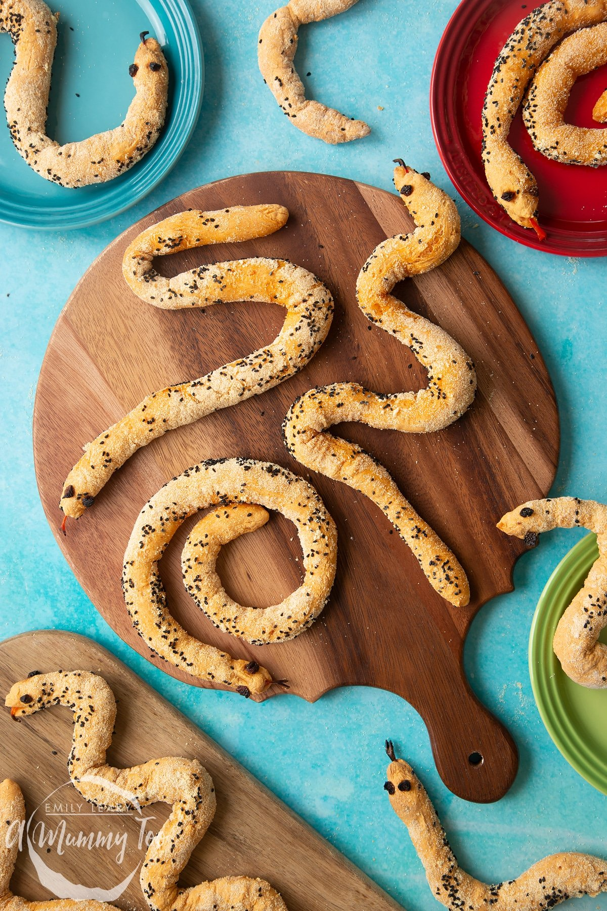 Bread snakes on a wooden board. More bread snakes are shown on coloured plates at the edges of the photo. each of the snakes wiggles in a different shape.