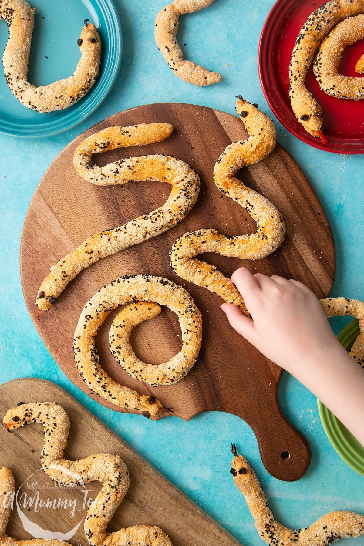 Bread snakes on a wooden board. More bread snakes are shown on coloured plates at the edges of the photo. A hand reaches to take a snake.