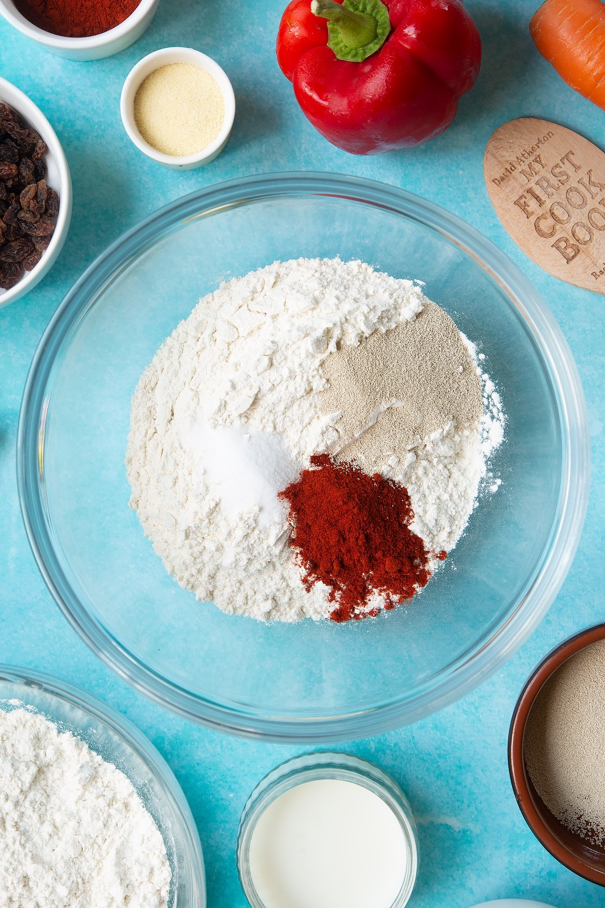 Flour, salt, paprika and yeast in a mixing bowl. Ingredients to make bread snakes surround the bowl.