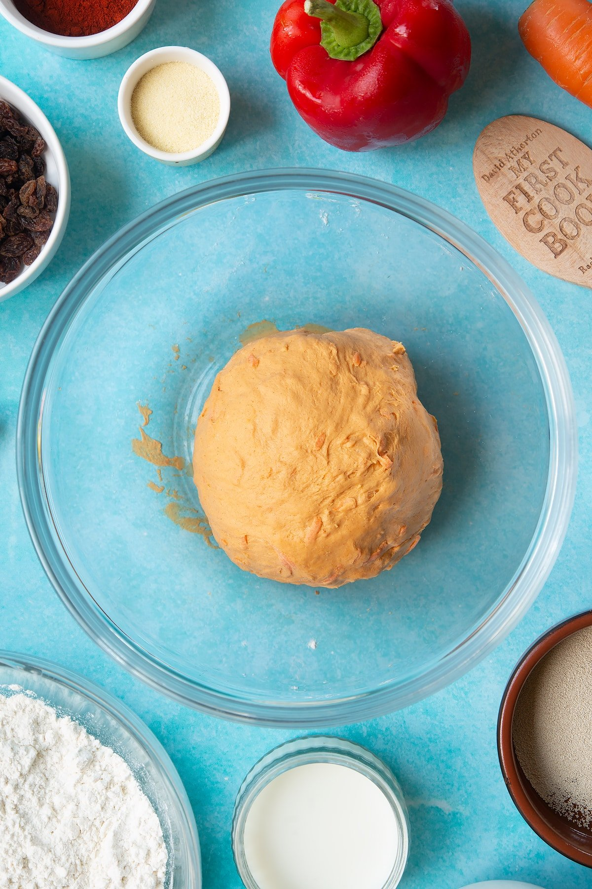 Kneaded paprika and carrot bread dough in a bowl. Ingredients to make bread snakes surround the bowl.