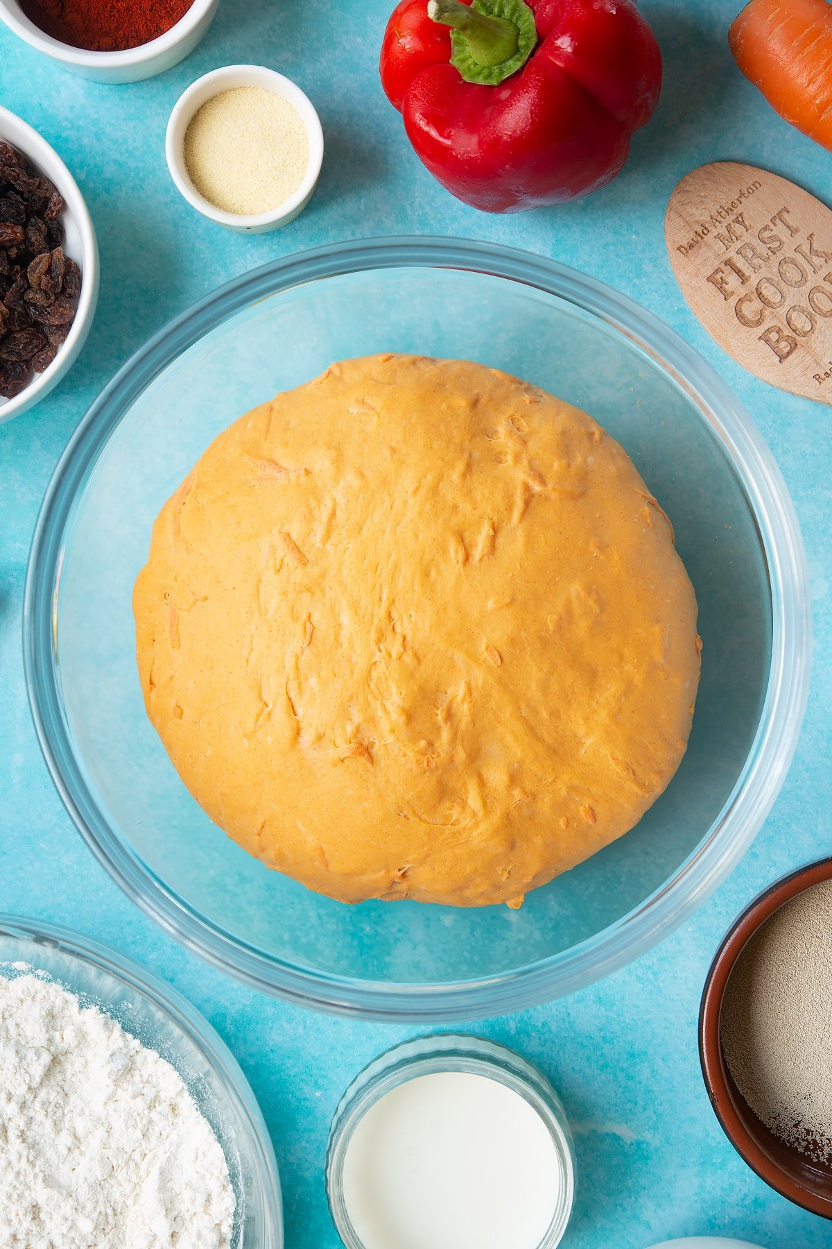 Proved paprika and carrot bread dough in a bowl. Ingredients to make bread snakes surround the bowl.