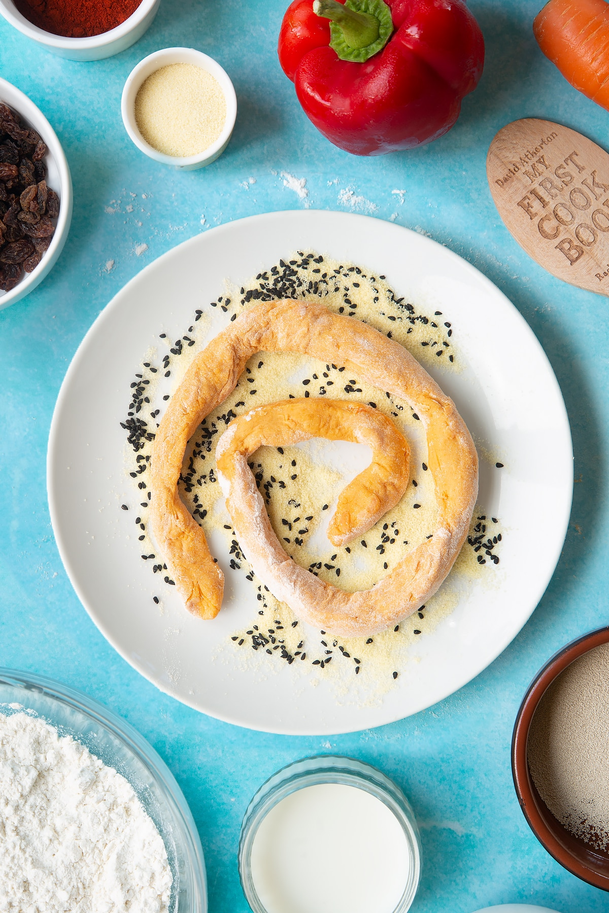 Paprika and carrot bread dough rolled into a long sausage on a plate with semolina and nigella seeds. Ingredients to make bread snakes surround the plate.
